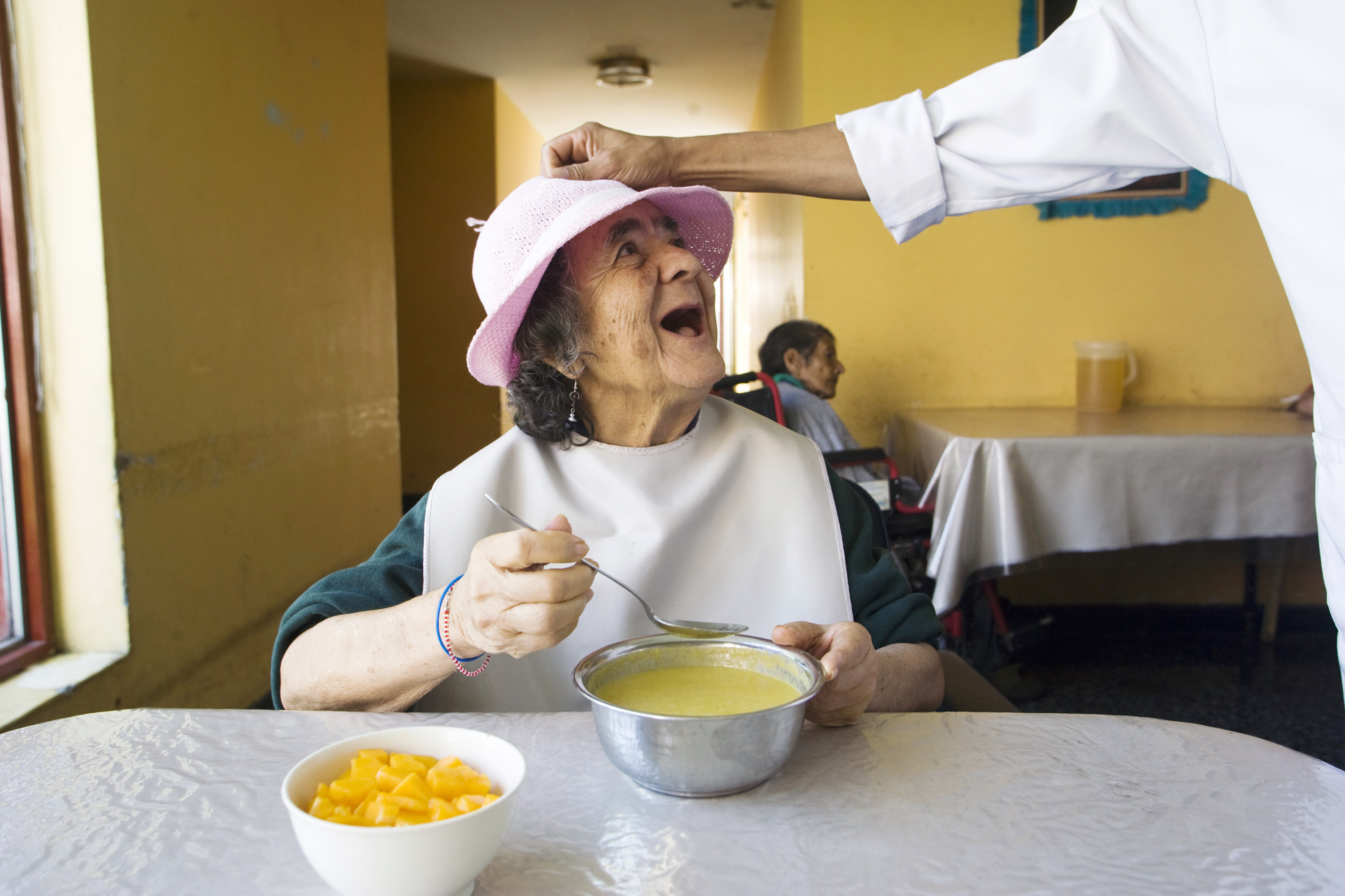 An elderly woman smiles while joking with a nurse during her lunch at the Canevaro old people's home in Lima March 25, 2010. This public institution is one the biggest in its kind in Latin America, hosting almost 400 elderly people, including dependent patients and those with senile dementia. 90 percent of its population are in abandon condition and more than the half used to live in extreme poverty, according to Canevaro's Director, Felipe Aguirre. Picture taken March 25, 2010. REUTERS/Enrique Castro-Mendivil (PERU - Tags: HEALTH SOCIETY IMAGES OF THE DAY) - GM1E63R03HL01