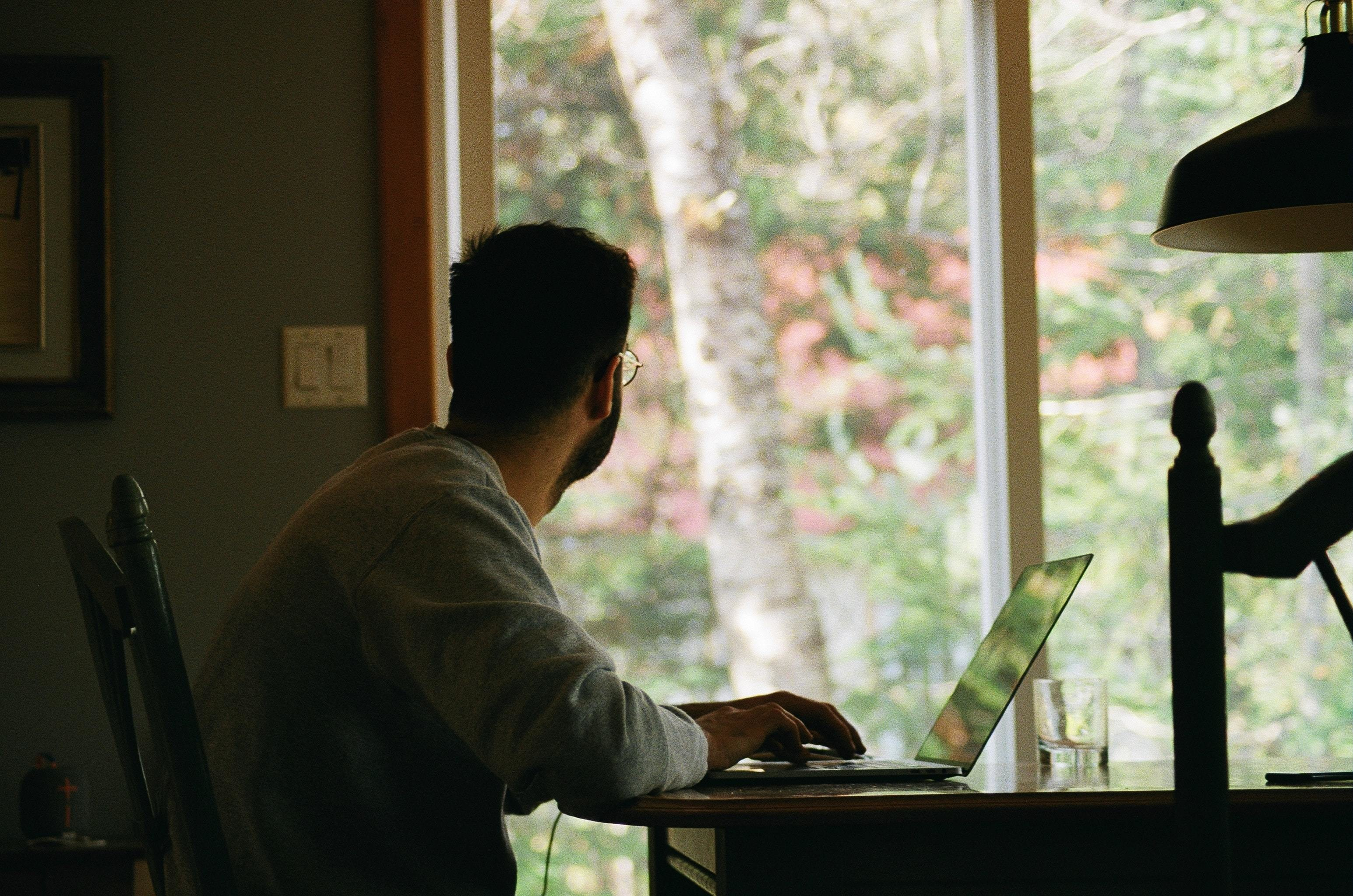 A man working from home looks away from his screen to gaze at the outside world