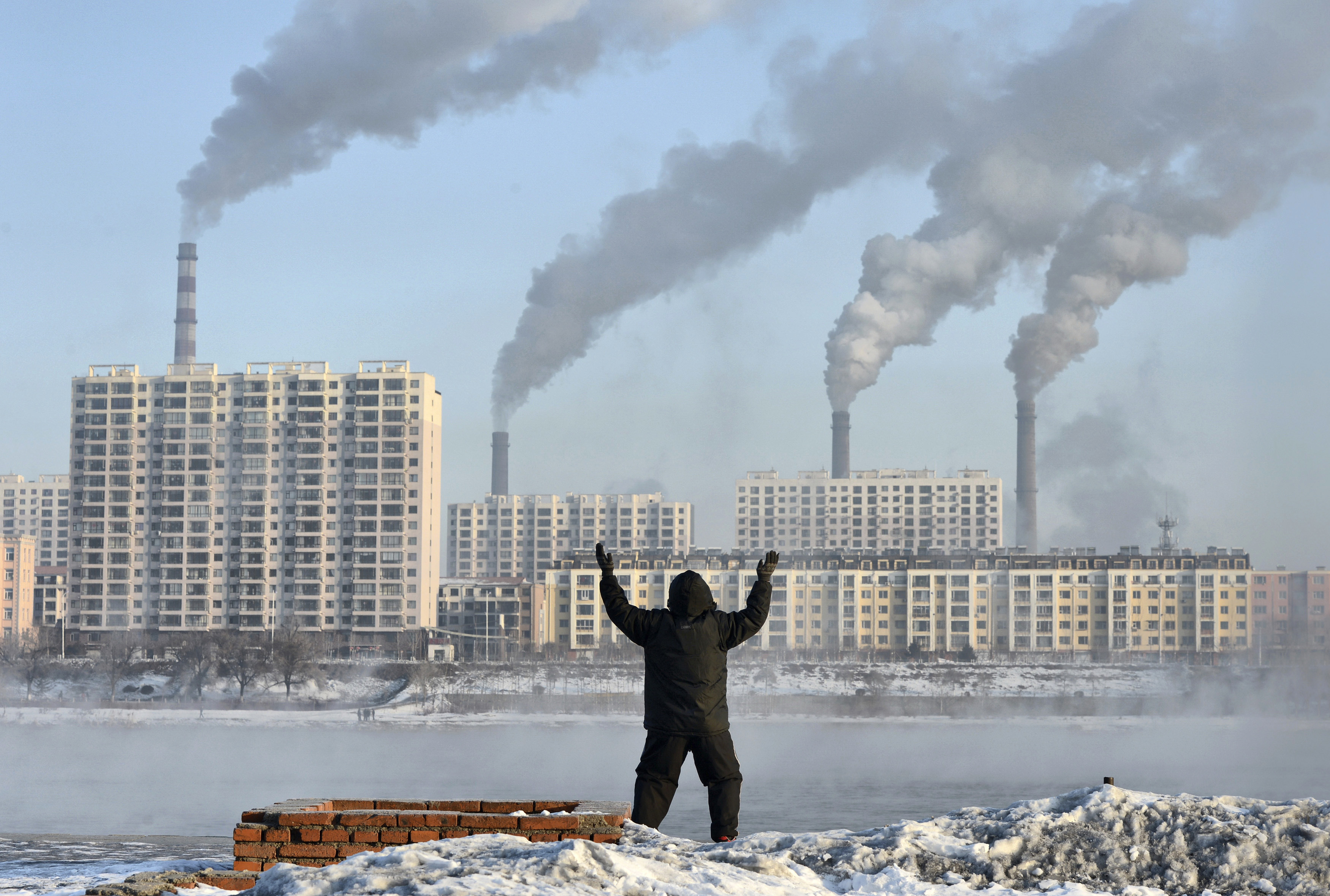 An elderly man exercises in the morning as he faces chimneys emitting smoke behind buildings across the Songhua river in Jilin, Jilin province, February 24, 2013. China's new rulers will focus on consumer-led growth to narrow the gap between rich and poor while taking steps to curb pollution and graft, the government said on Tuesday, tackling the main triggers for social unrest in the giant nation. Picture taken February 24, 2013. REUTERS/Stringer (CHINA - Tags: ENVIRONMENT BUSINESS POLITICS) CHINA OUT. NO COMMERCIAL OR EDITORIAL SALES IN CHINA - GM1E9351DC501