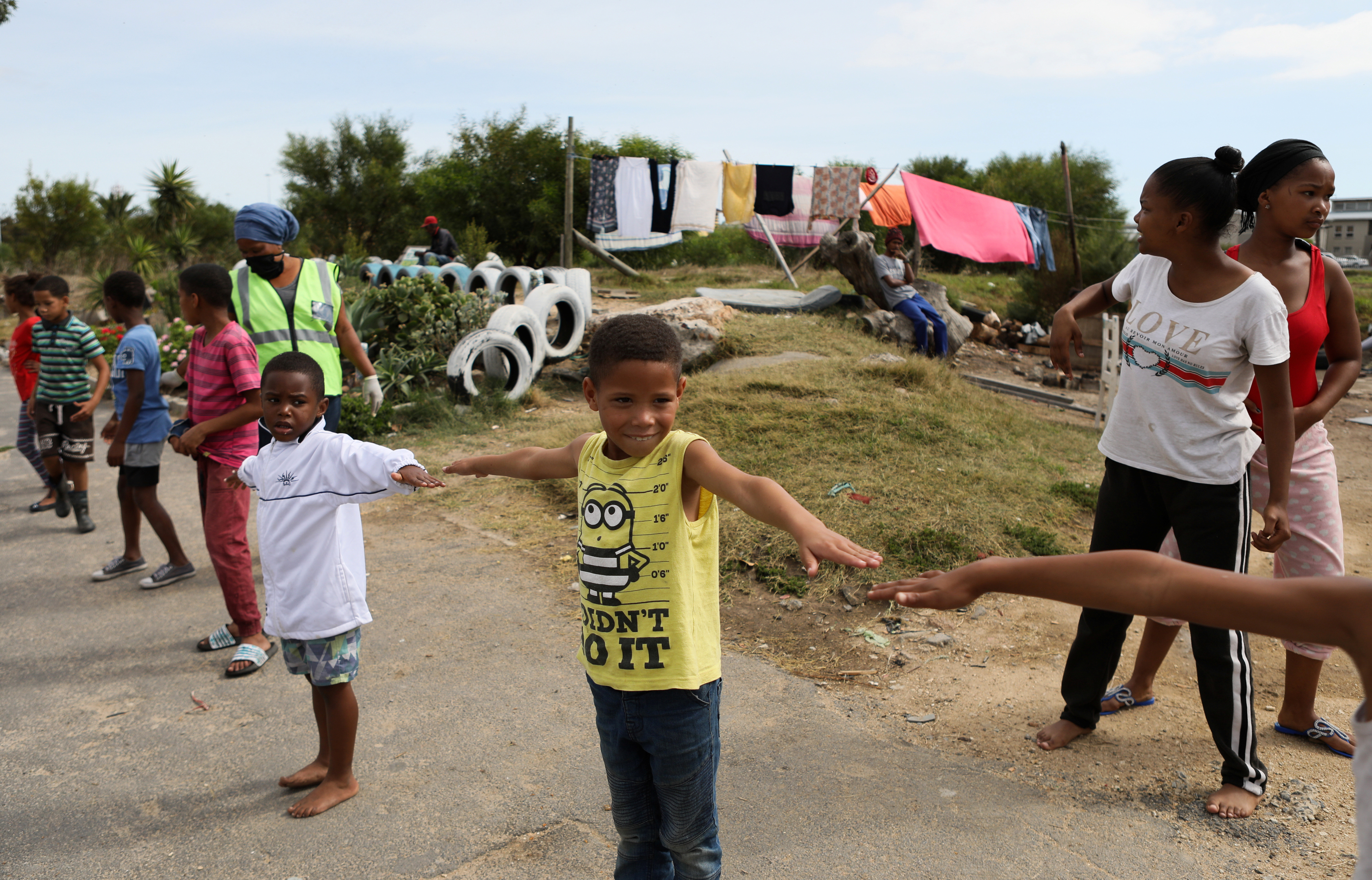 Children practice social distancing while the spread of the coronavirus disease (COVID-19) continues, in an informal settlement in Cape Town, South Africa, April 17, 2020. REUTERS/Sumaya Hisham - RC2F6G9EB0G8
