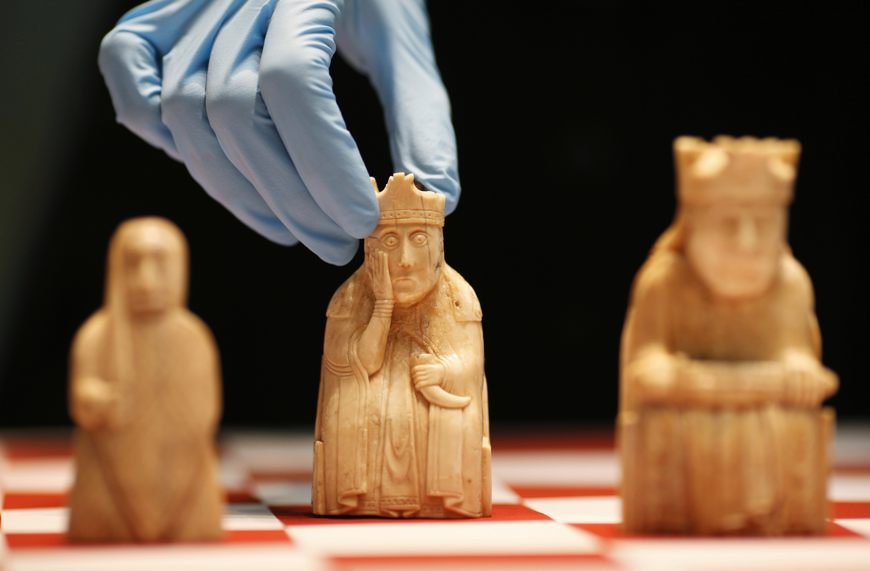 A worker at the British Museum arranges the Lewis Chessmen on a chess board in London March 16, 2009. The Lewis Chessmen, made of walrus ivory circa 1150-1200 AD, are among the museum's most popular objects and the most famous in the medieval collection and will form part of the exhibit in the museum's new medieval gallery.  REUTERS/Andrew Winning   (BRITAIN SOCIETY) - GM1E53G1U5901