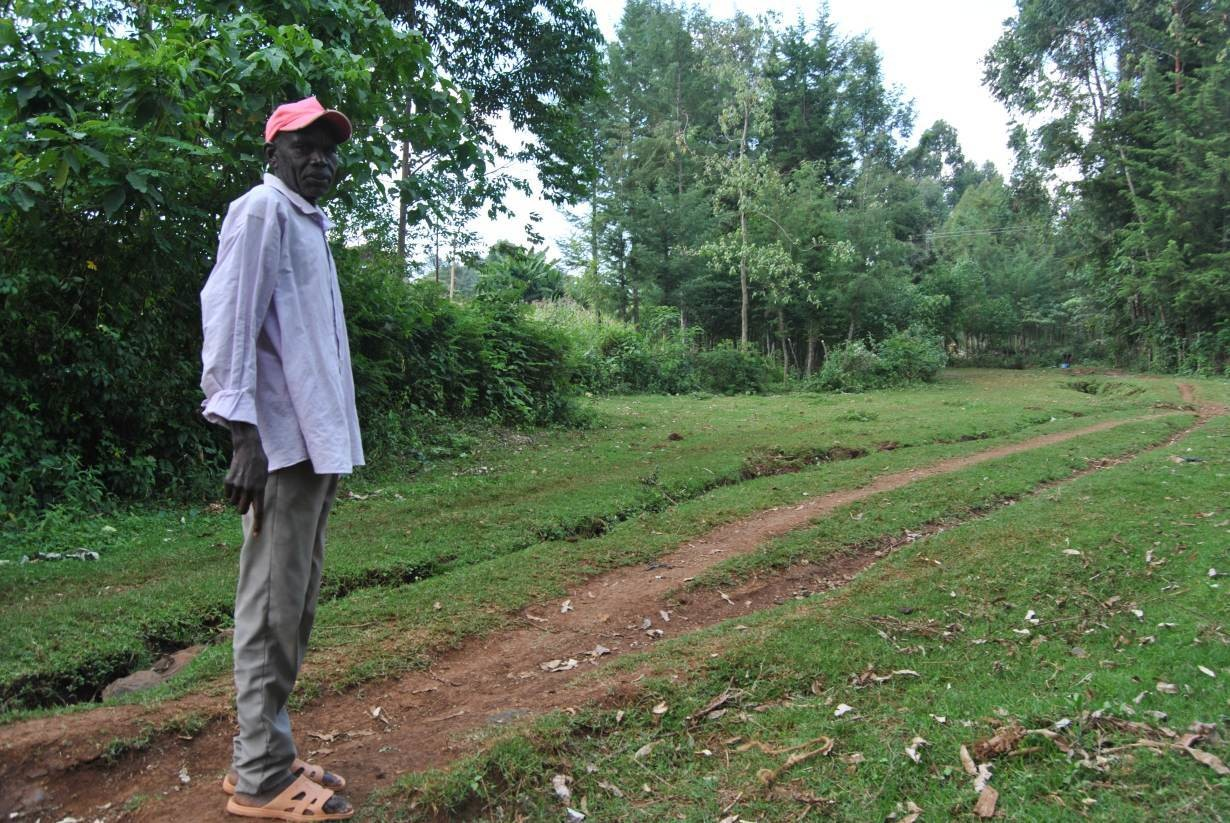 elder Julius Kosgei stands on what used to be an impassable river in Ainamoi village that is now dried up in Kenya's Kericho County