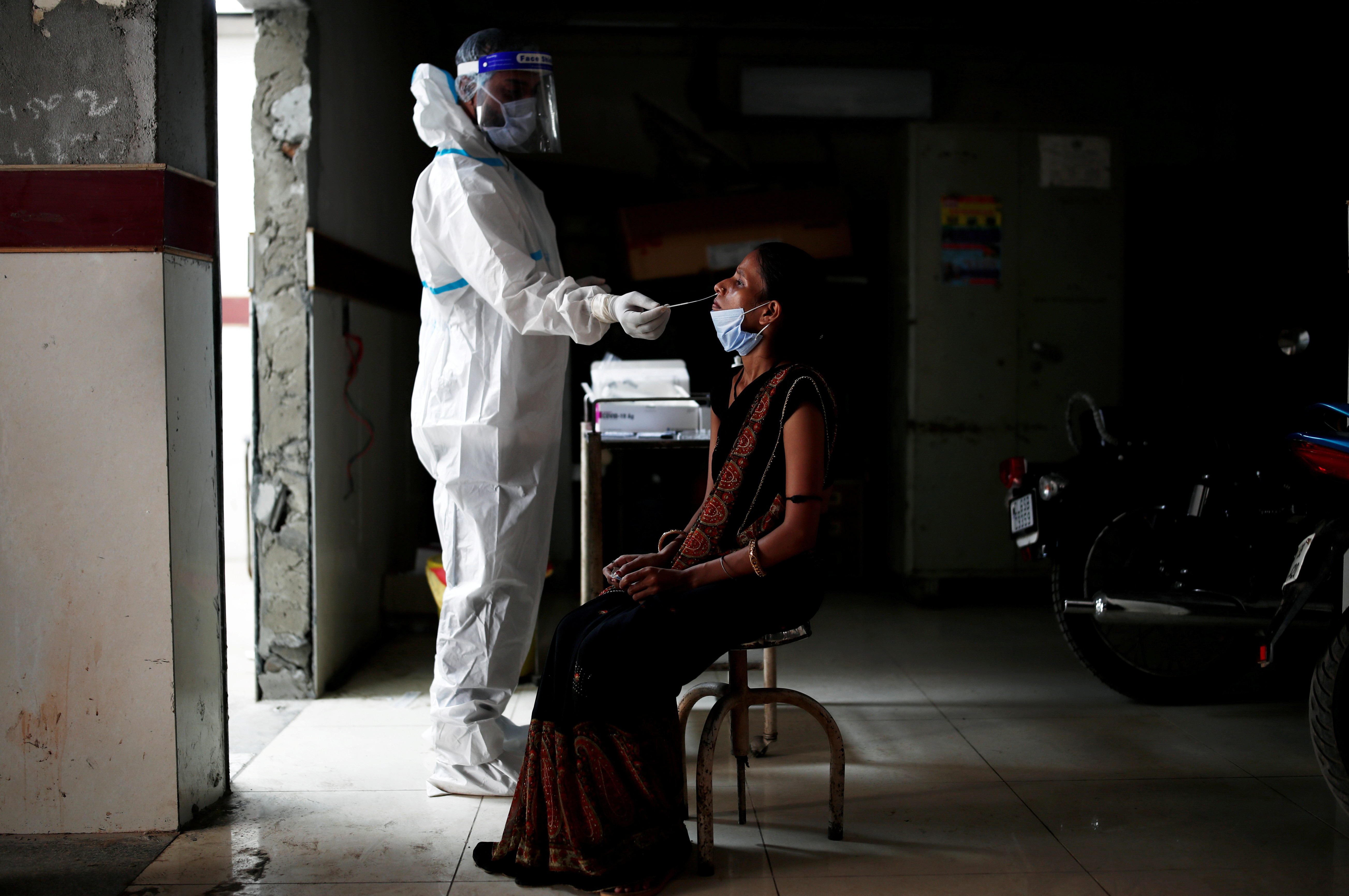 image of a medical health worker in personal protective equipment collecting a sample from a woman using a swab, at a local health centre to conduct tests for COVID19