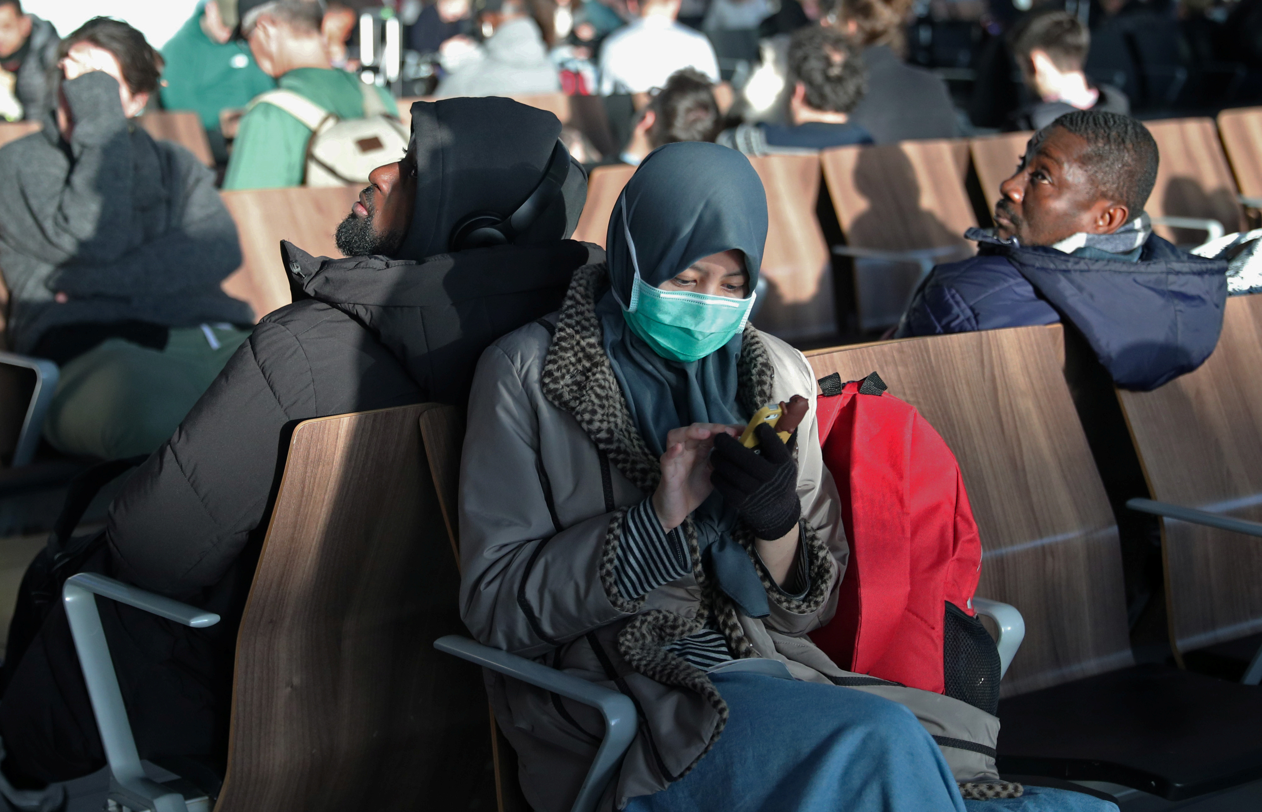 A woman wears a surgical mask as she sits in Terminal 5 at Heathrow Airport in London, Britain March 6, 2020. REUTERS/Hannah McKay - RC28EF9M4USC