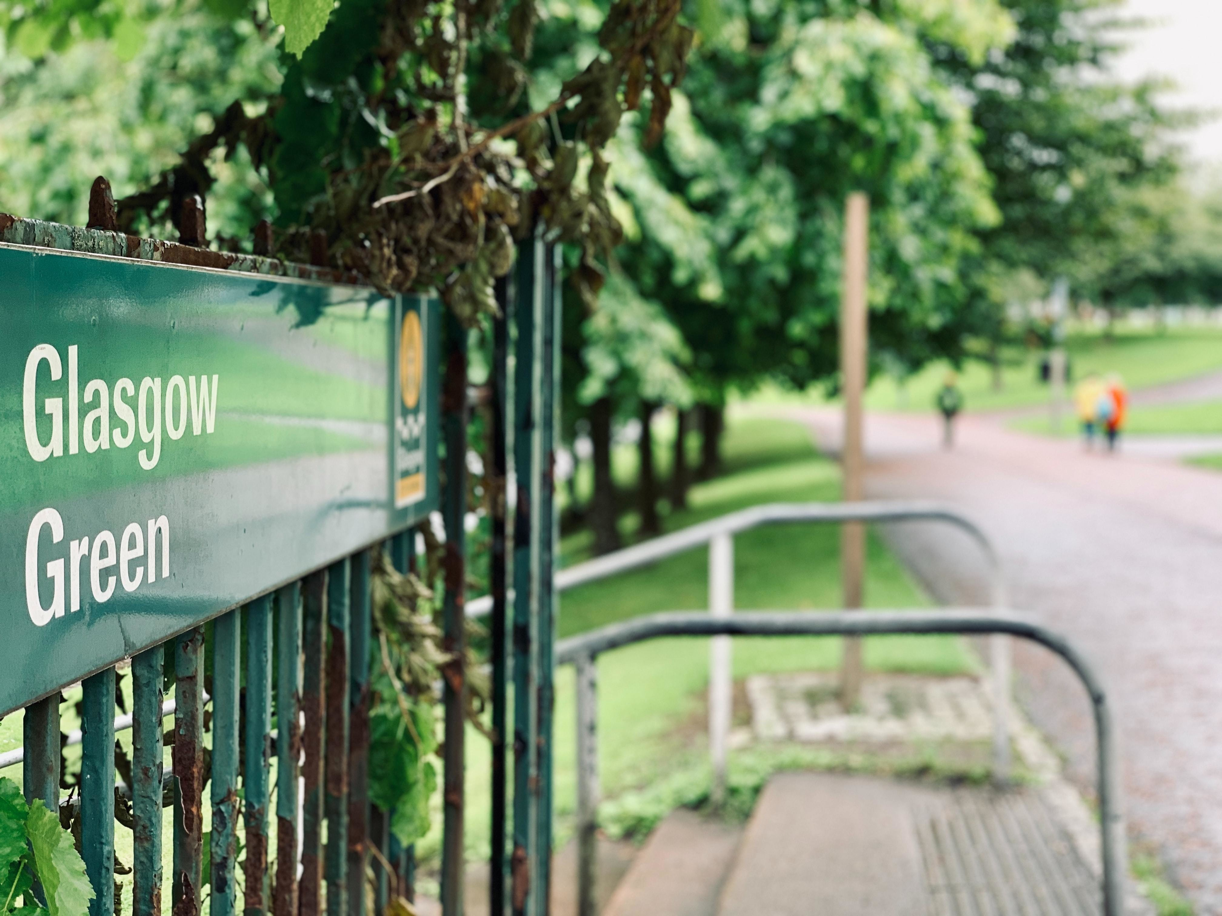 a picture of a sign in an urban green area saying Glasgow green