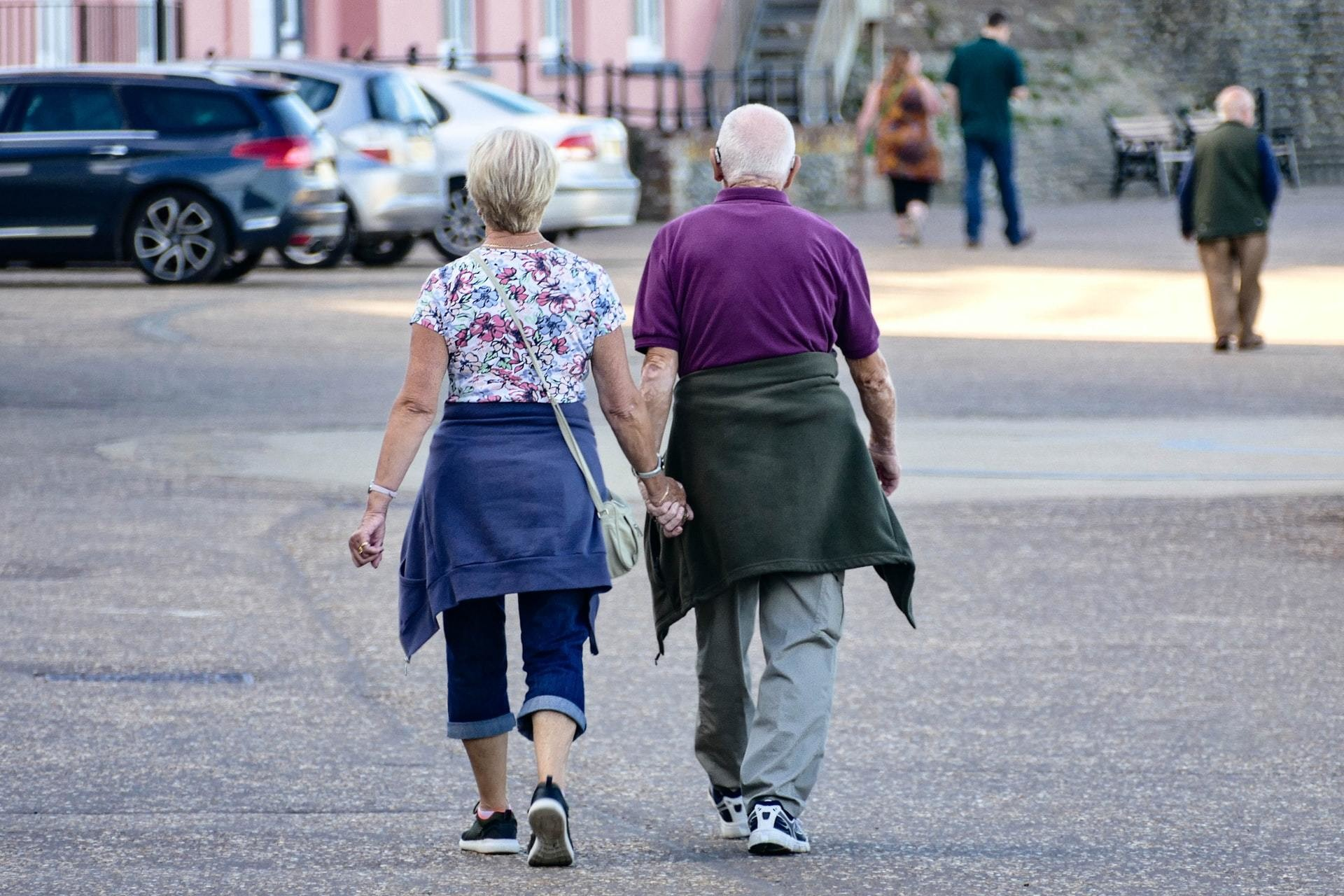 An ageing couple walking hand-in-hand down a street