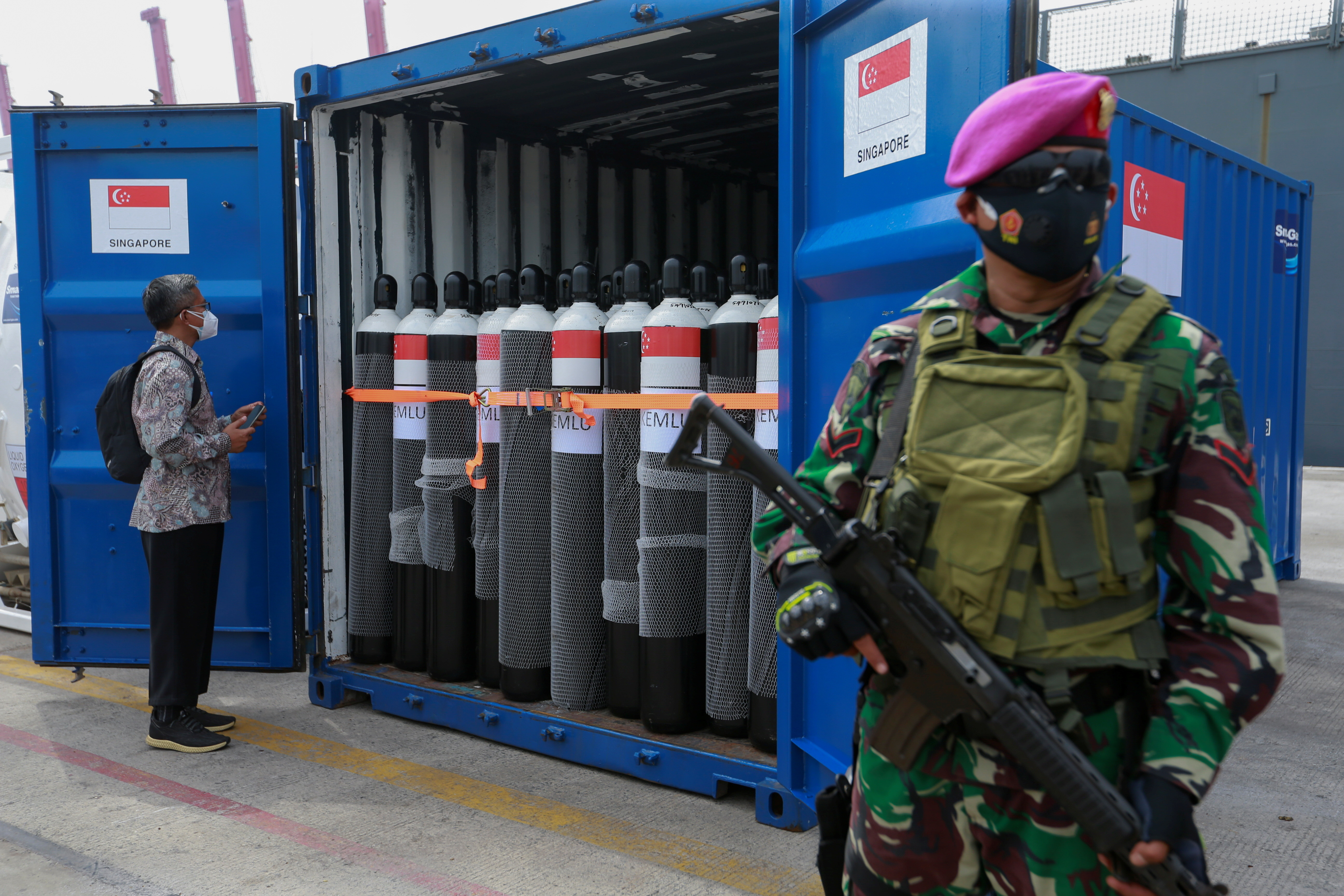 A Directorate General of Customs and Excise officer stands near an oxygen cylinder, while an Indonesian military official guards the medical supplies sent by the Singapore government amid a surge of coronavirus disease (COVID-19) cases in Jakarta, Indonesia, July 14, 2021. REUTERS/Ajeng Dinar Ulfiana - RC26KO94TVR4