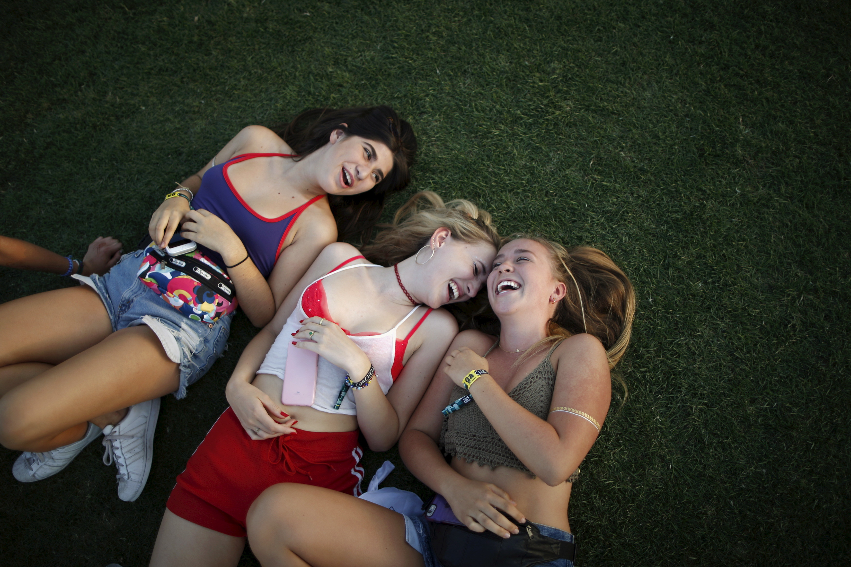 Women lie on the grass to listen to Hozier at the Coachella Valley Music and Arts Festival in Indio, California April 11, 2015. REUTERS/Lucy Nicholson - GF10000056660