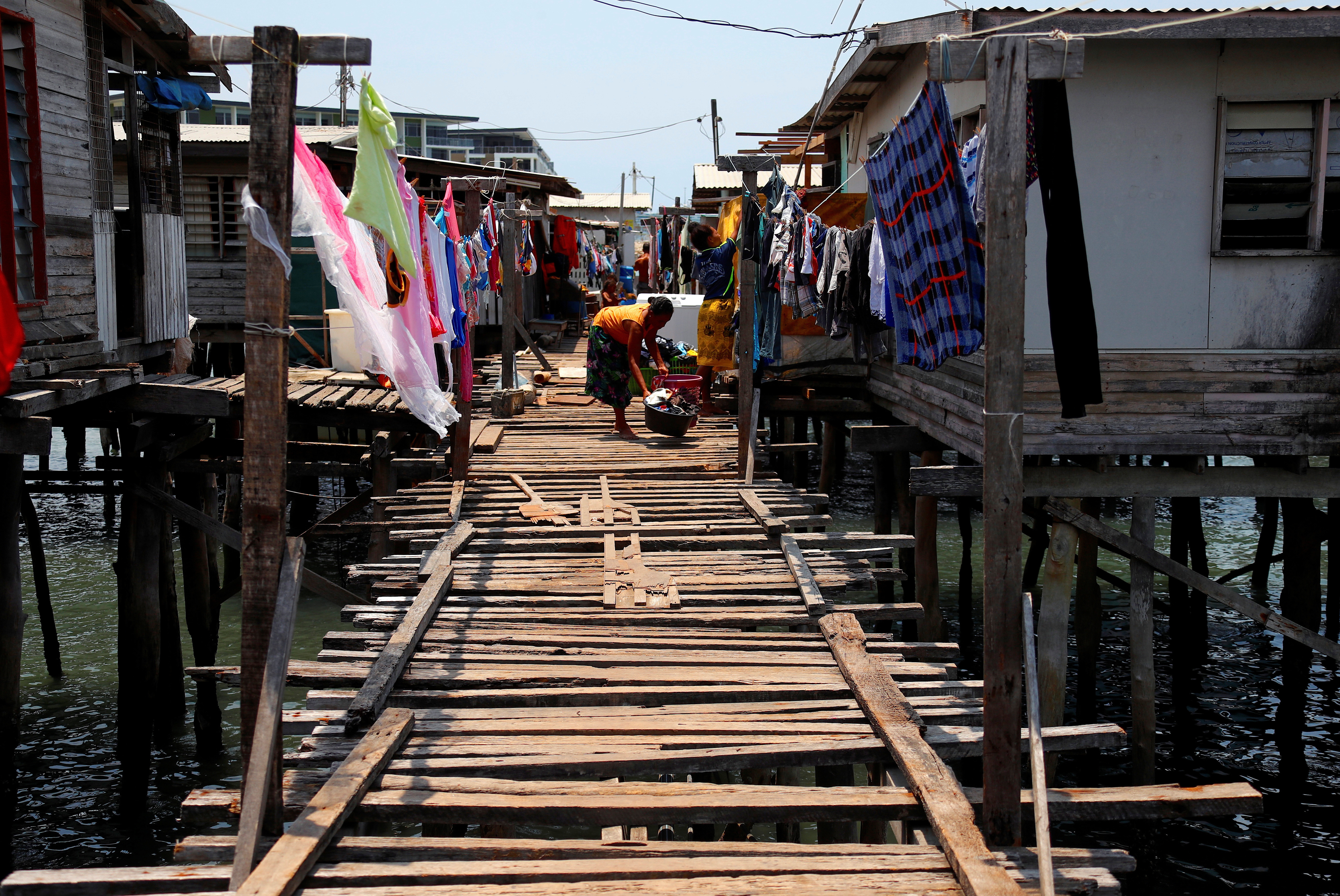 A woman washes clothes on a wooden path between stilt houses at Hanuabada Village, located in Port Moresby Harbour, Papua New Guinea, November 19, 2018. Picture taken November 19, 2018.       REUTERS/David Gray - RC1542BE3E00
