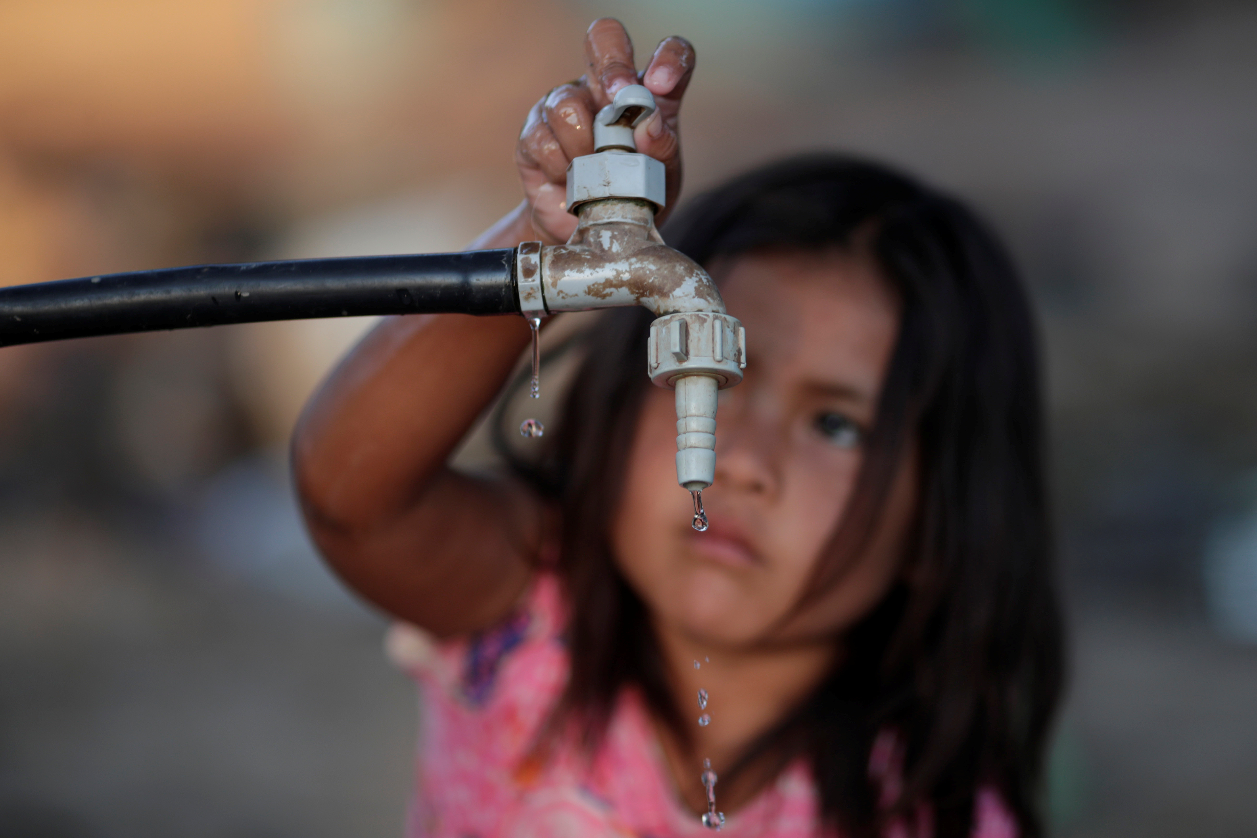 a child turns off a water tap
