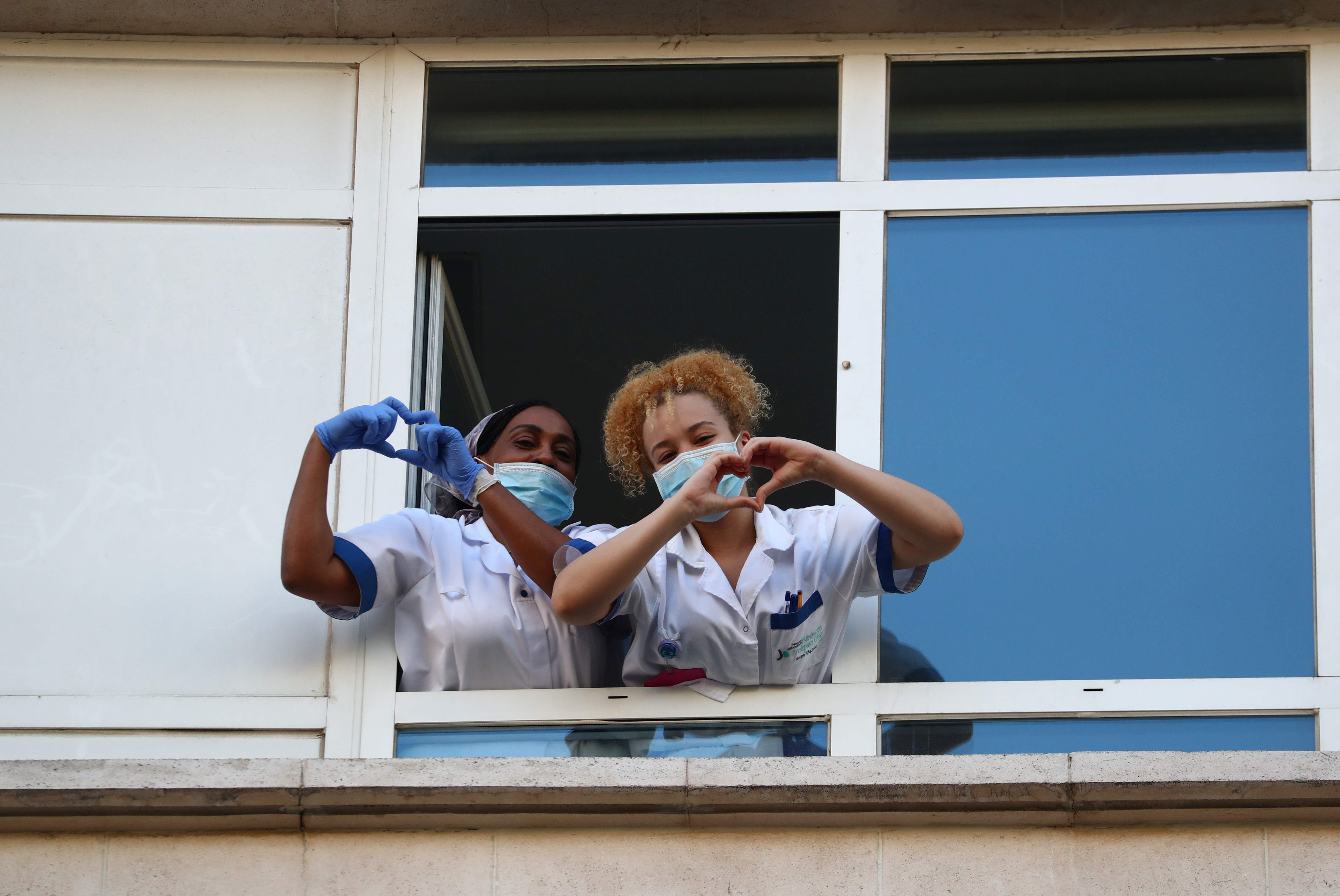 Medical staff from Fundacion Jimenez Diaz hospital make a heart gesture with their hands, while people applaud from their balconies in support for healthcare workers, as it is expected to be the last day of applauses, amid the coronavirus disease (COVID-19) outbreak, in Madrid, Spain, May 17, 2020