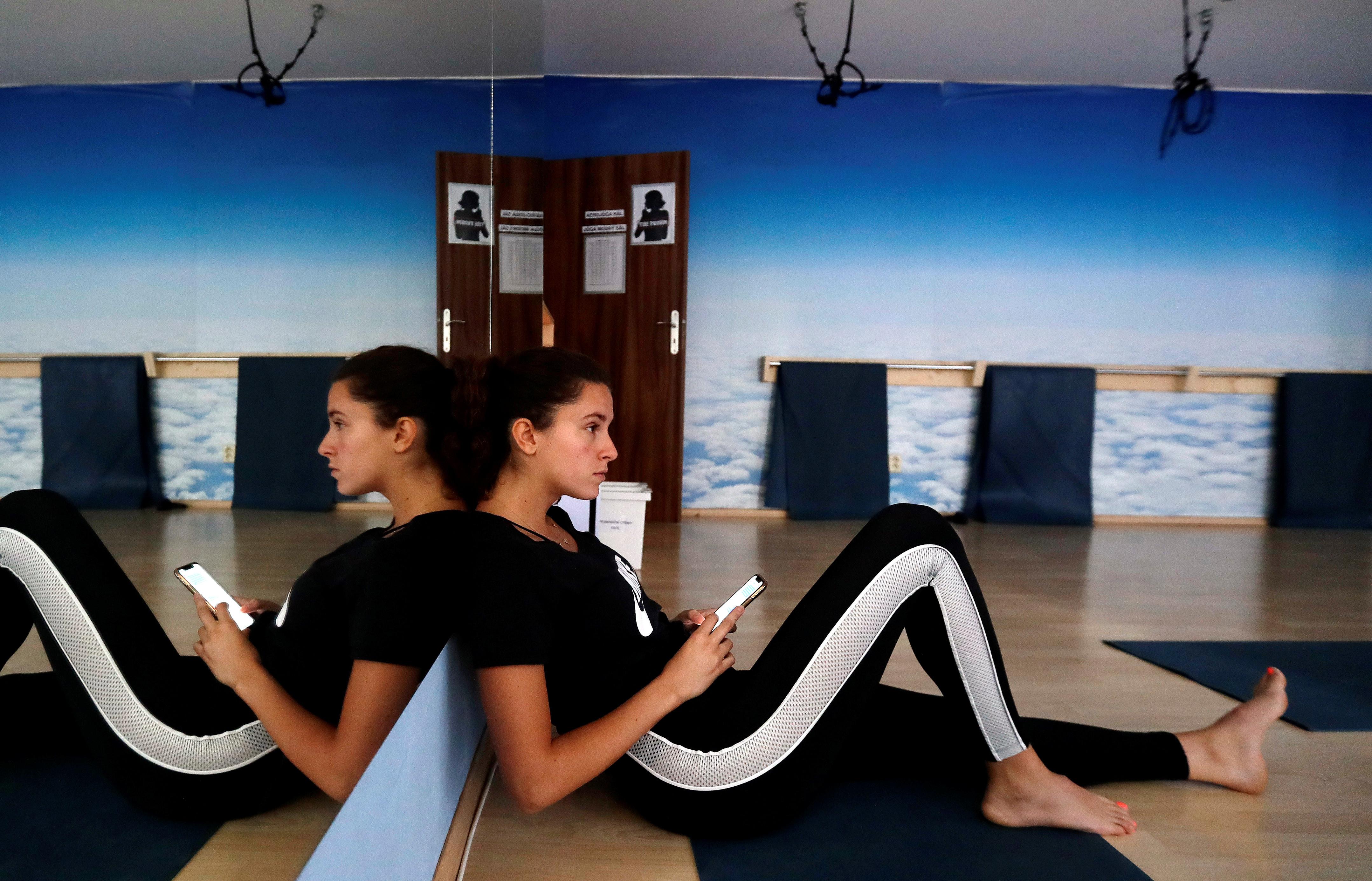 Dunia Skaunicova, a 24 years old job seeker, checks her mobile phone as she waits for a yoga class following the coronavirus disease (COVID-19) outbreak, in Prague, Czech Republic, July 8, 2020. Picture taken July 8, 2020. REUTERS/David W Cerny - RC2IPH9IB1BL
