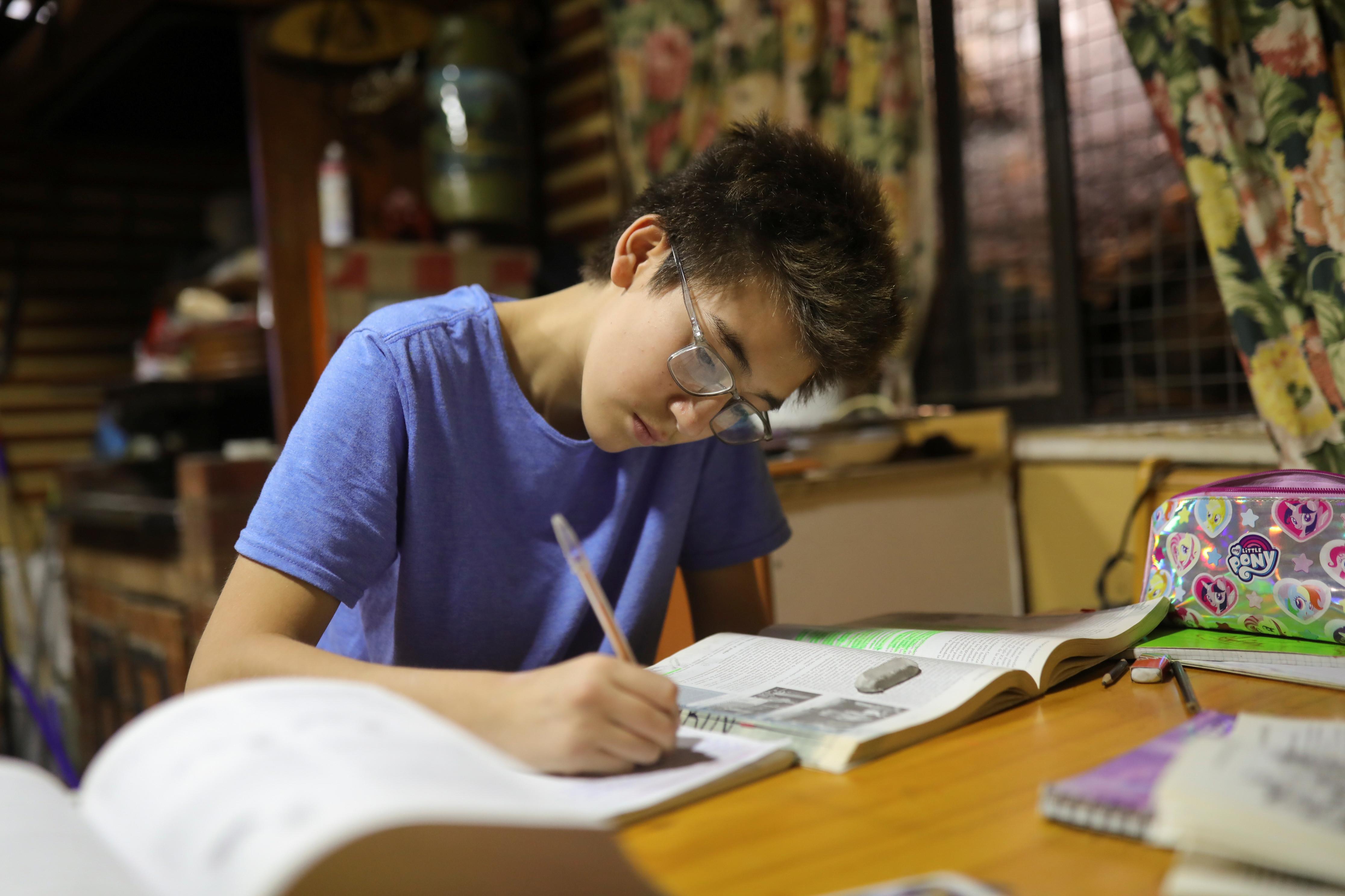a teenager sits doing his homework