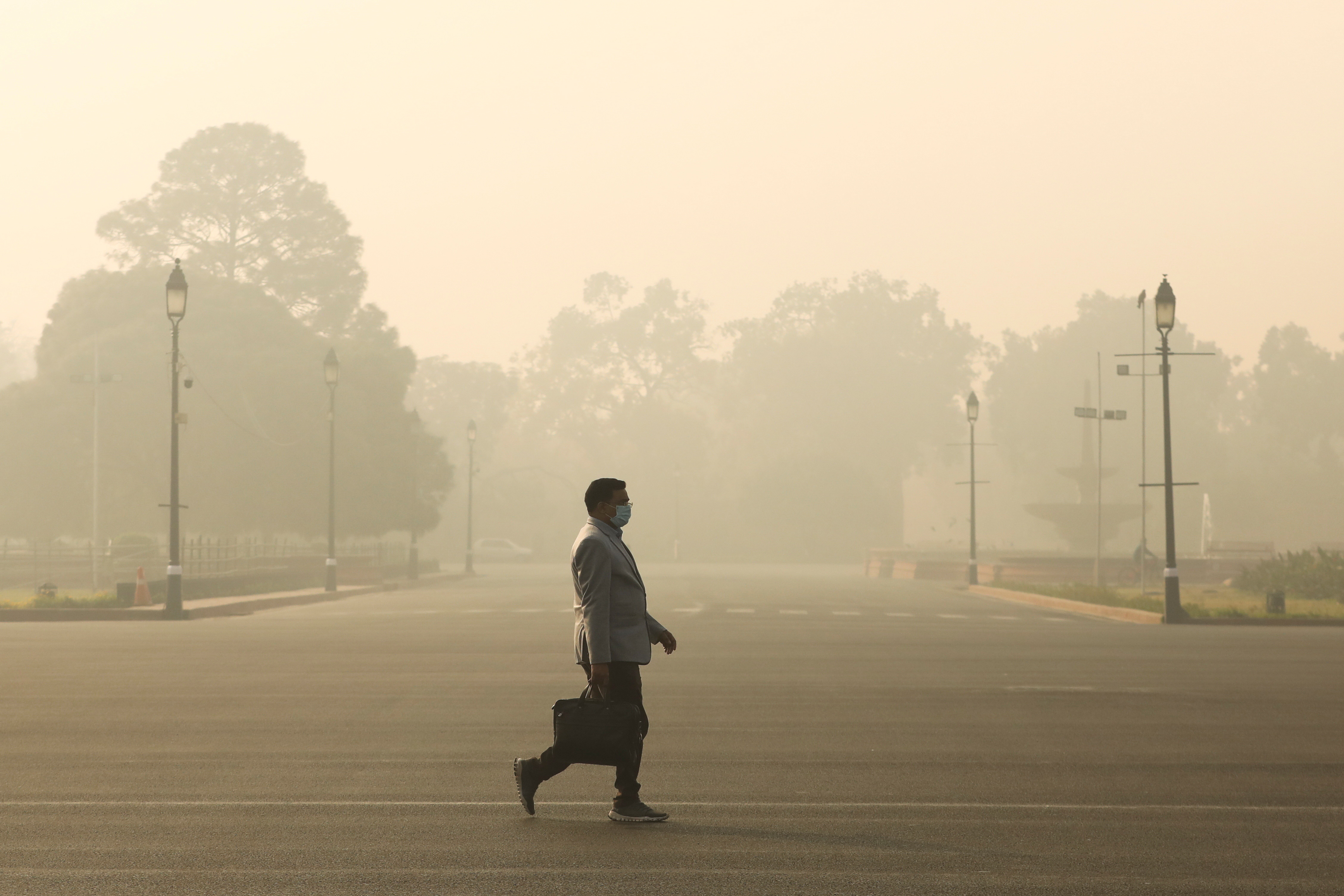 A man walks along a road on a smoggy morning in New Delhi, India, December 23, 2020. REUTERS/Anushree Fadnavis - RC2USK970CV1