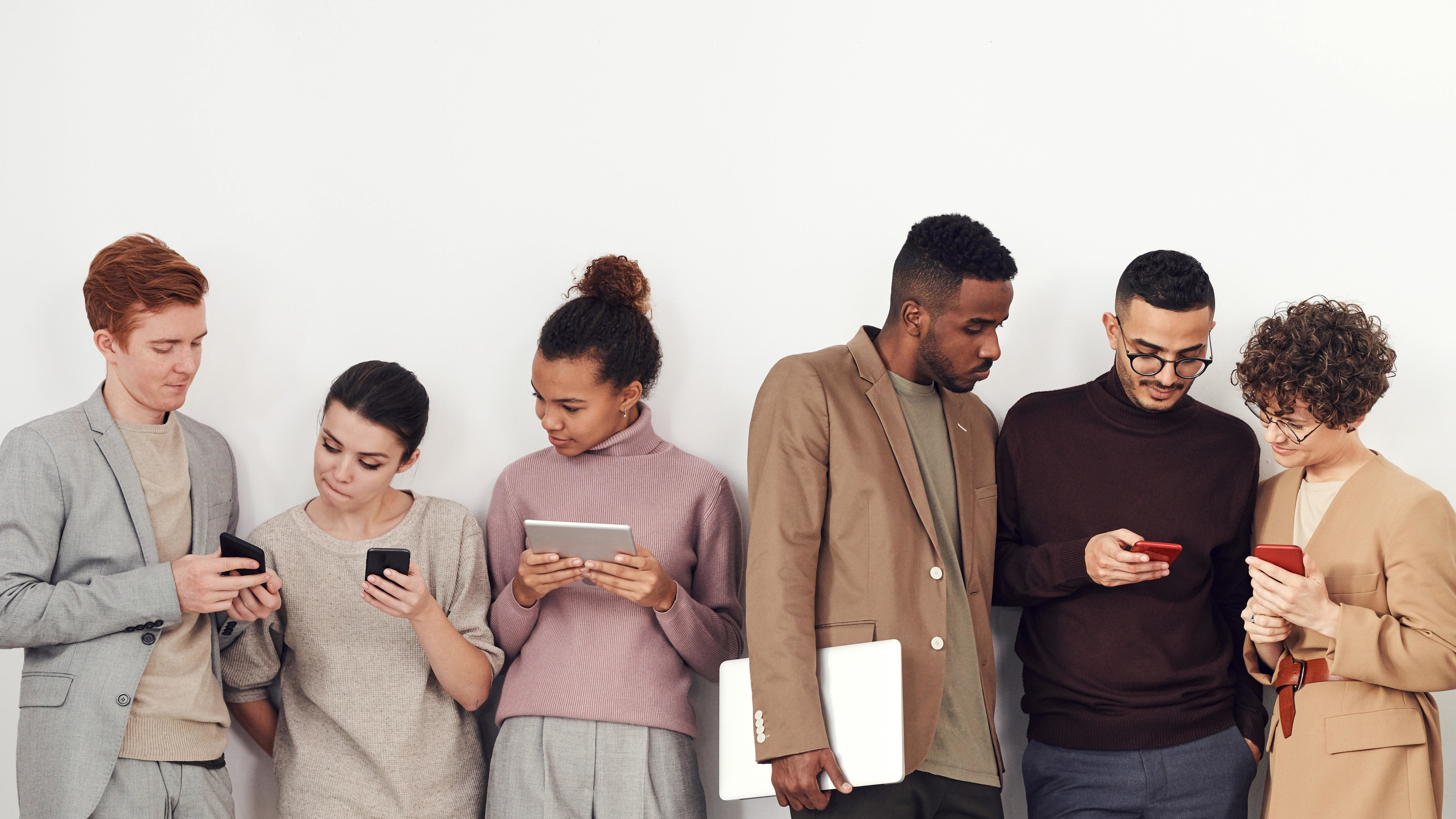 Group of people looking at their mobile phones.