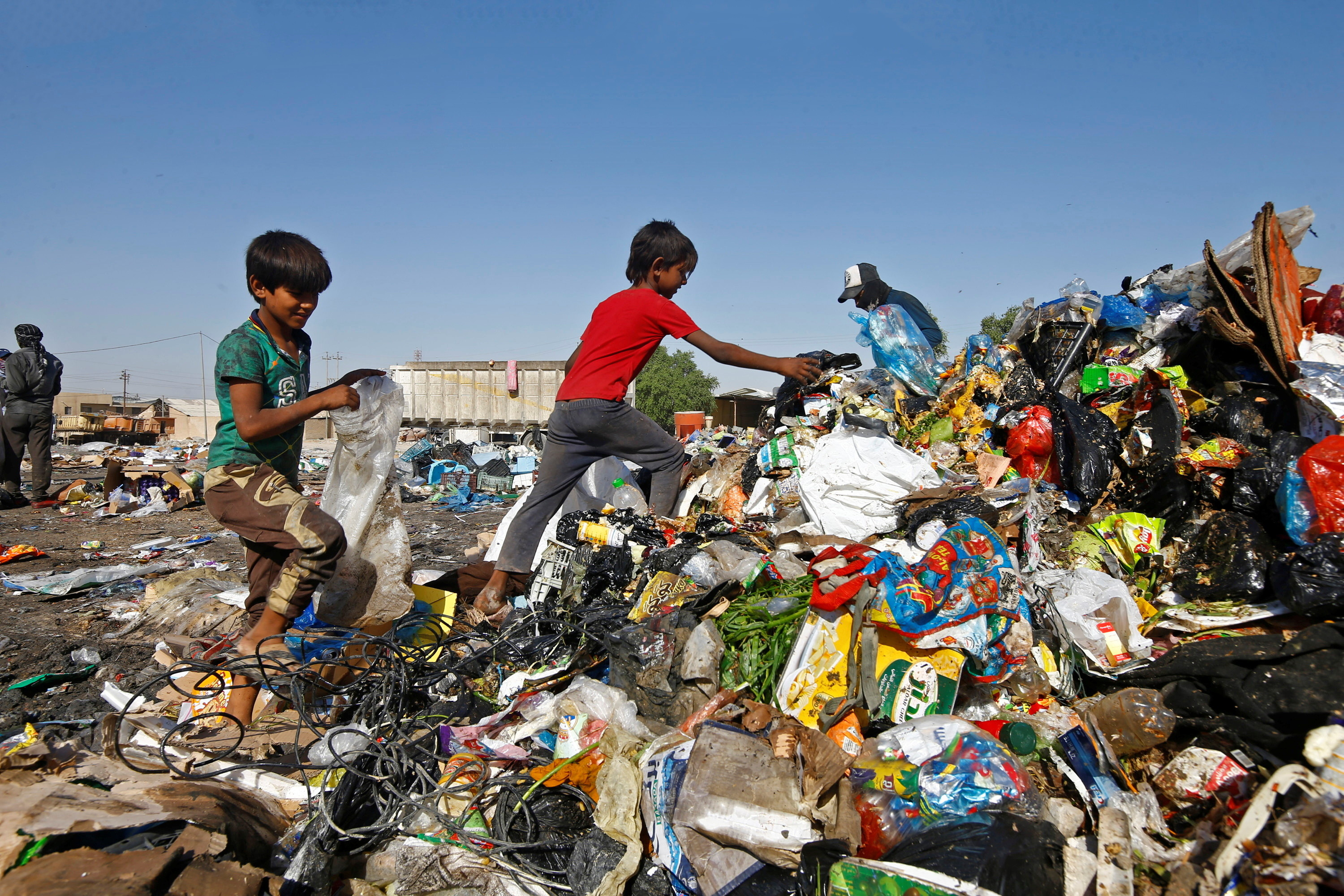 two boys collect rubbish at a tip