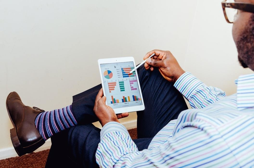 image of a businessman looking at graphs and pie charts on a tablet