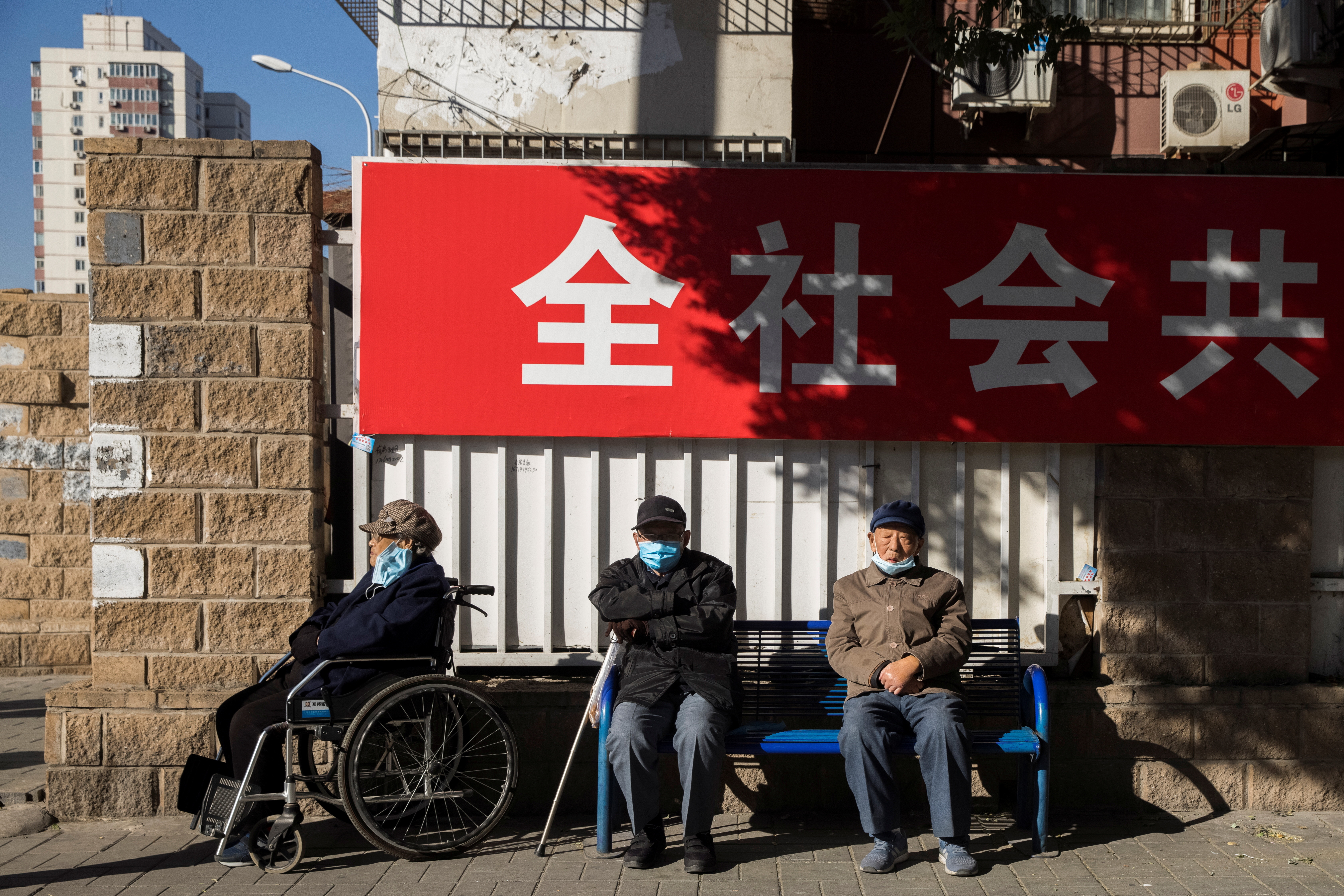 Elderly people sit in a street during morning rush hour following an outbreak of the coronavirus disease (COVID-19) in Beijing, China, November 3, 2020.   REUTERS/Thomas Peter - RC2GVJ9NU878