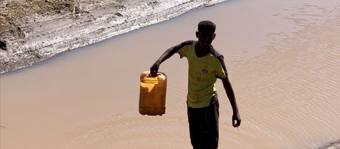 A man fetches water from a canal in Sudan.