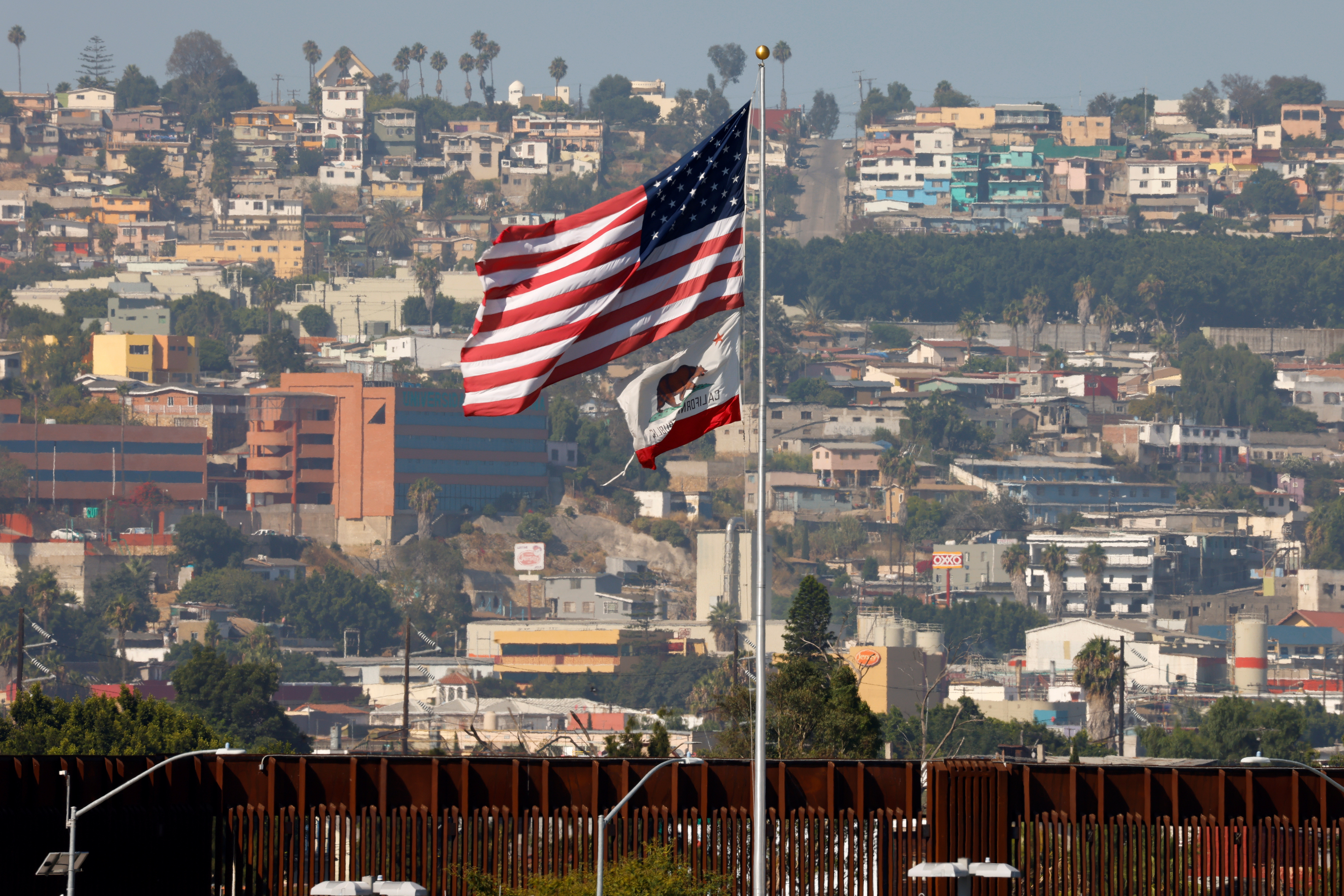 The state flag of California and the U.S. flag fly next to the border wall near Tijuana, Mexico, and during the outbreak of coronavirus disease (COVID-19), in San Diego, California, U.S., August 14, 2020.      REUTERS/Mike Blake - RC2WDI95XDYW