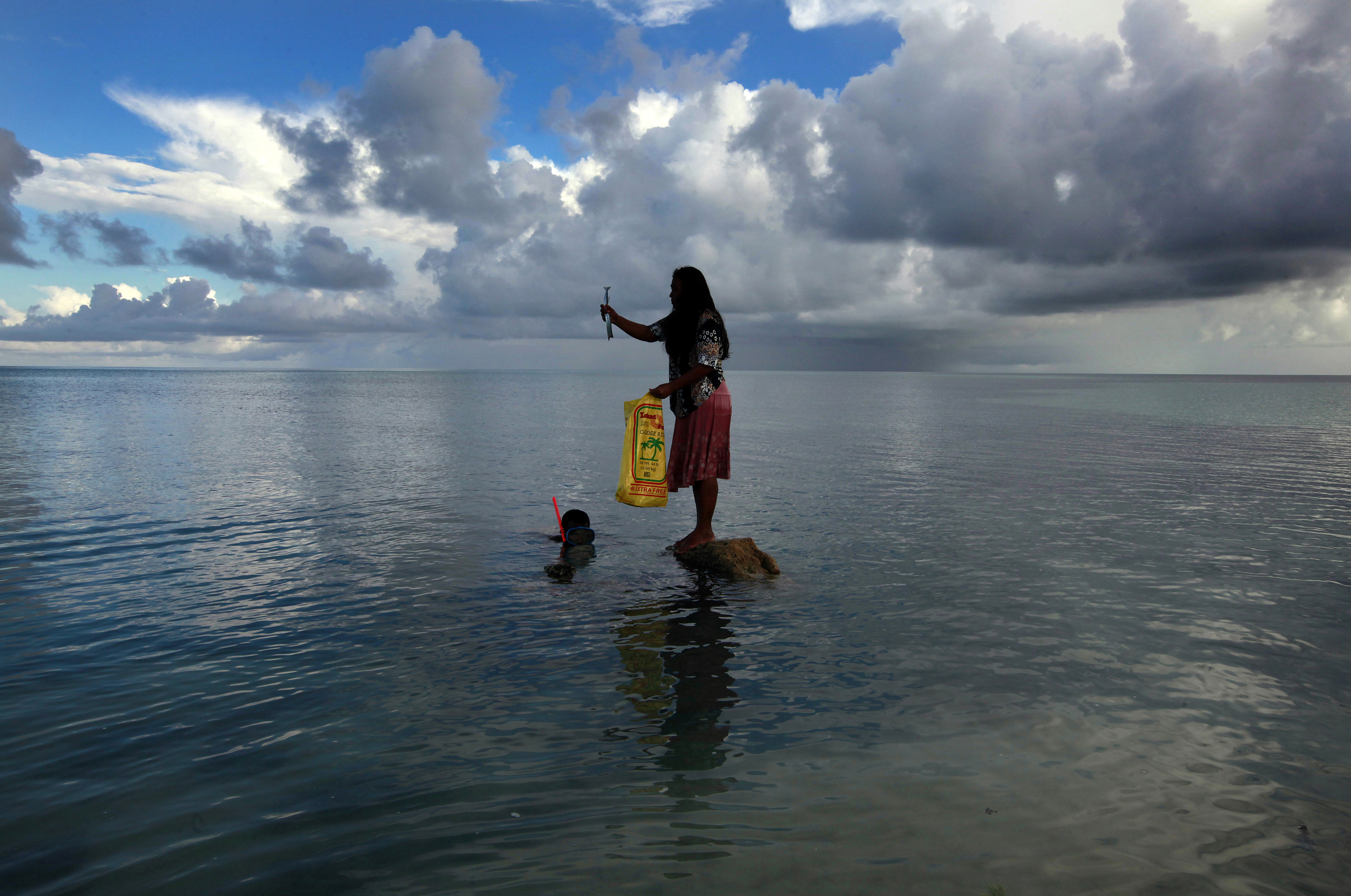 a woman fishes in the sea
