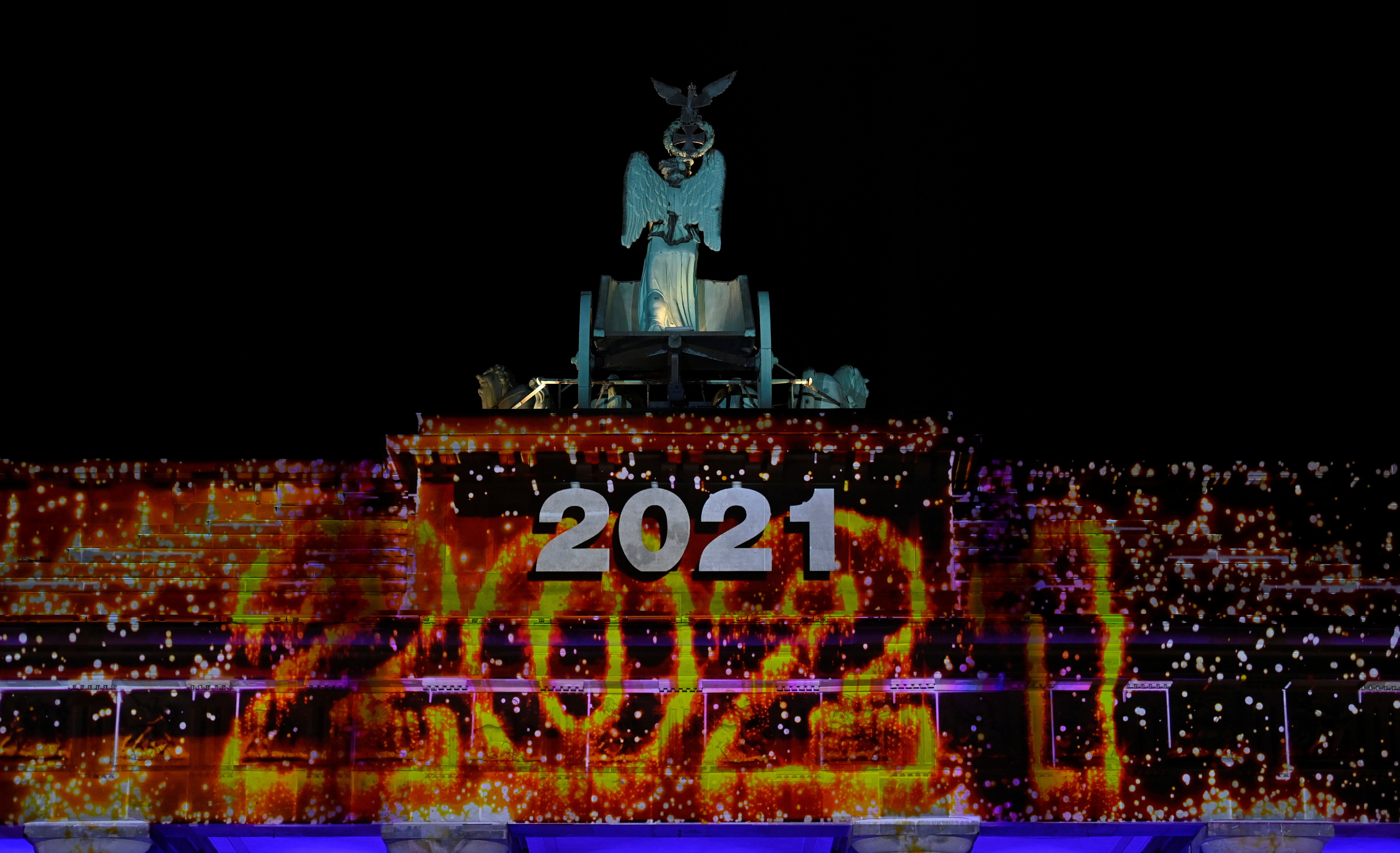 "Berlin's landmark Brandenburg Gate is illuminated with the lettering ""2021""' at the start of a concert ""Willkommen 2021"" (Welcome 2021) amid coronavirus disease (COVID-19) restrictions in Berlin, Germany December 31, 2020. Picture taken December 31, 2020. John Macdougall/Pool via REUTERS - RC20ZK9USC8Q"