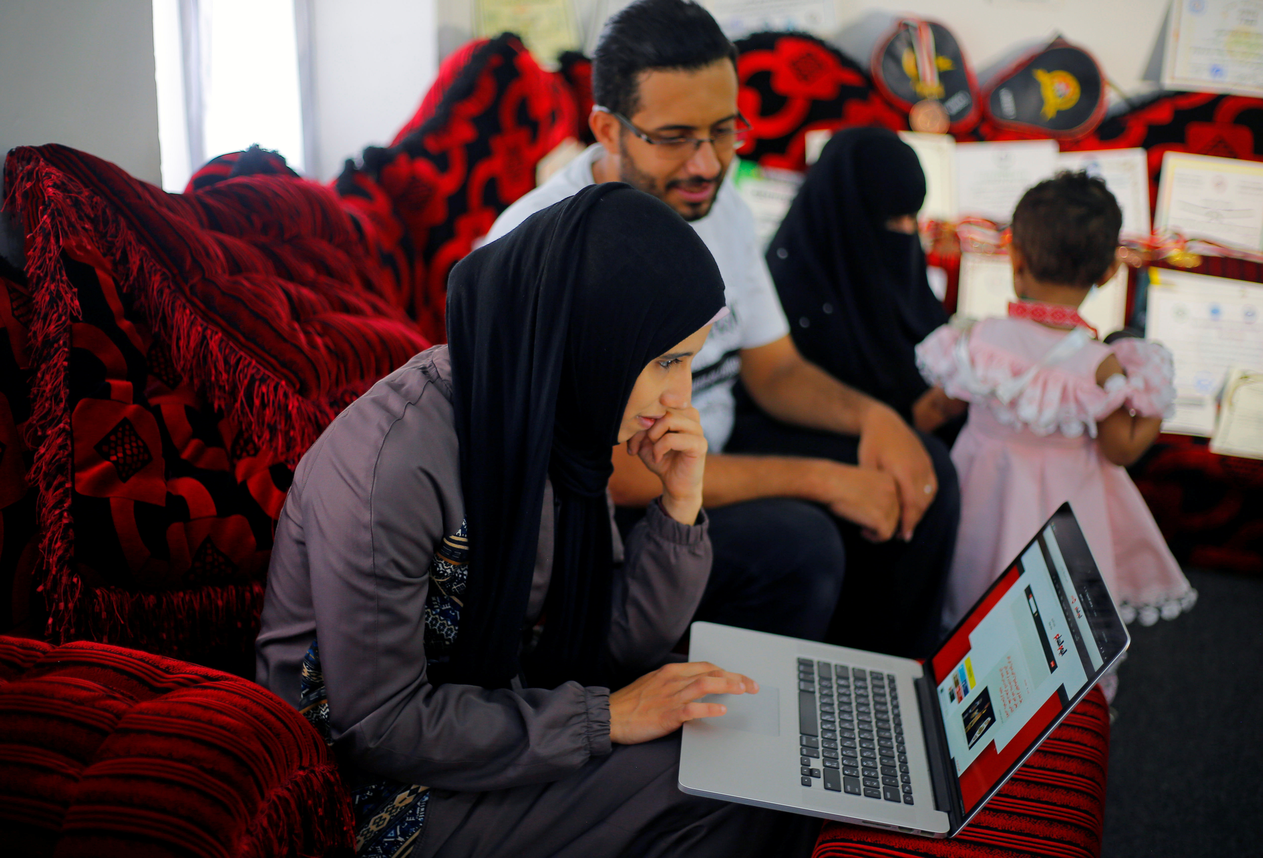 Martial arts trainer Seham Amer checks work on the computer as she sits with relatives at her home in Sanaa, Yemen September 3, 2020. Picture taken September 3, 2020. REUTERS/Nusaibah Almuaalemi - RC2OVI9VISNC