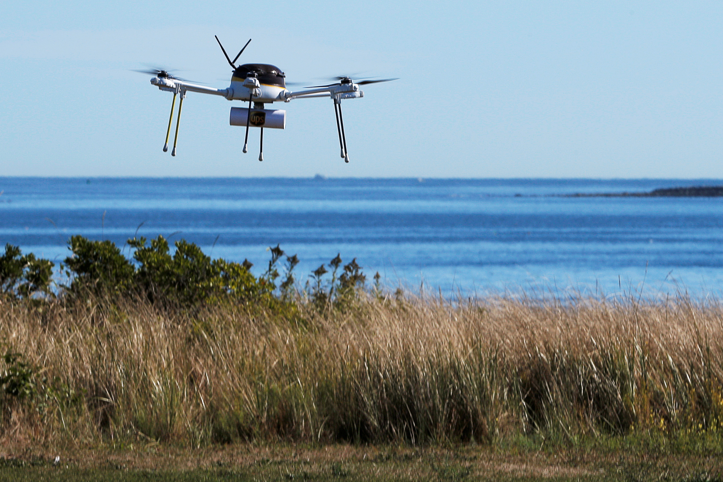A drone, made by CyPhy Works, delivers a UPS package on Children's Island off the coast of Beverly, Massachusetts, U.S. September 22, 2016, during UPS's demonstration of a drone making a commercial delivery of a package to a remote or difficult-to-access location. Picture taken September 22, 2016. REUTERS/Brian Snyder  - S1BEUCYKOTAA
