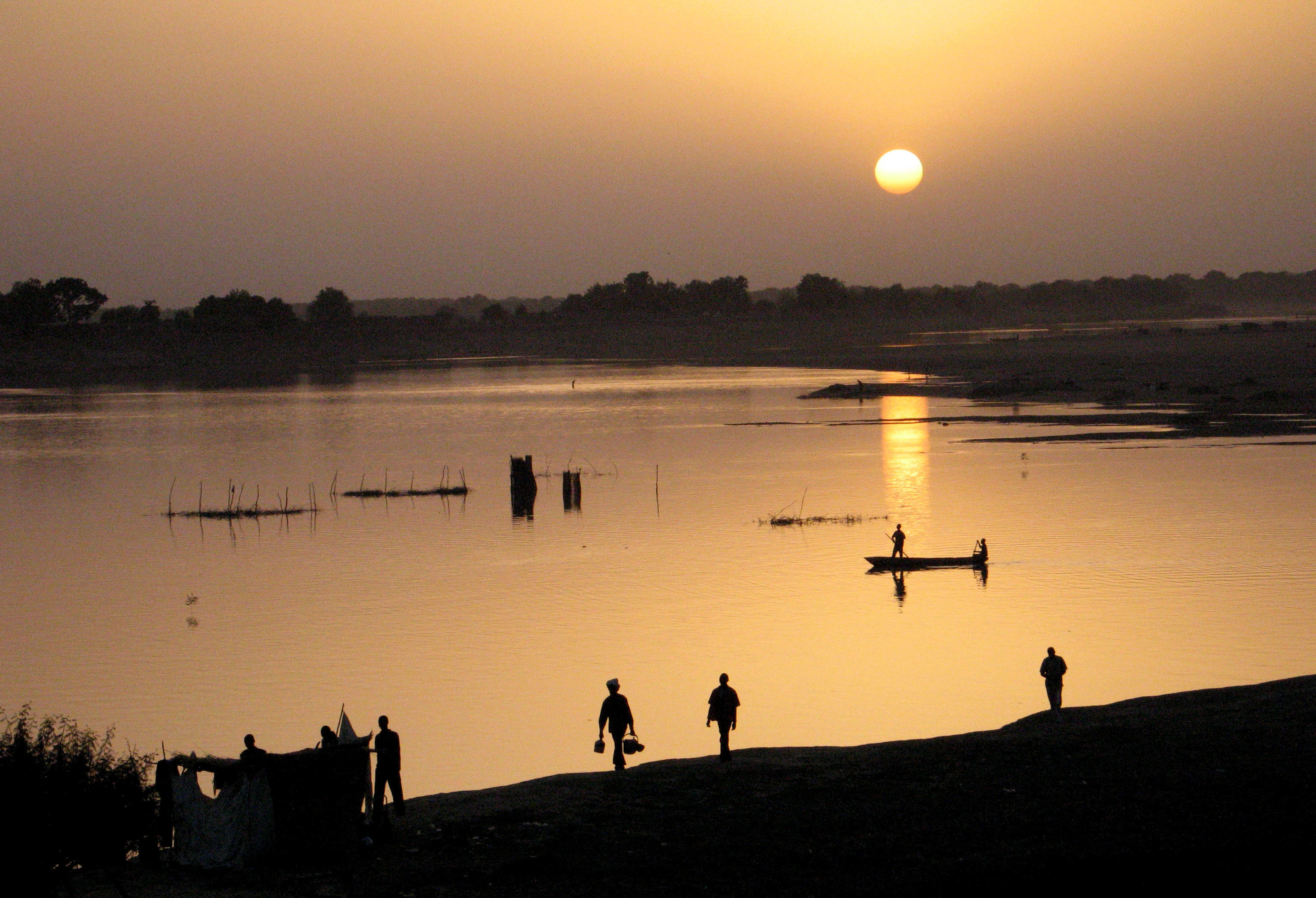 Fishermen return home at sunset in Chad's capital N'djamena April 21, 2006. A five-member team on an African union mission to Chad arrived in the country on Friday to probe President Idriss Deby's accusations that neighbour Sudan is backing rebels bent on ending his nearly 16-year rule. Picture taken April 21, 2006. REUTERS/David Mwangi - GF1DSLDYBNAA