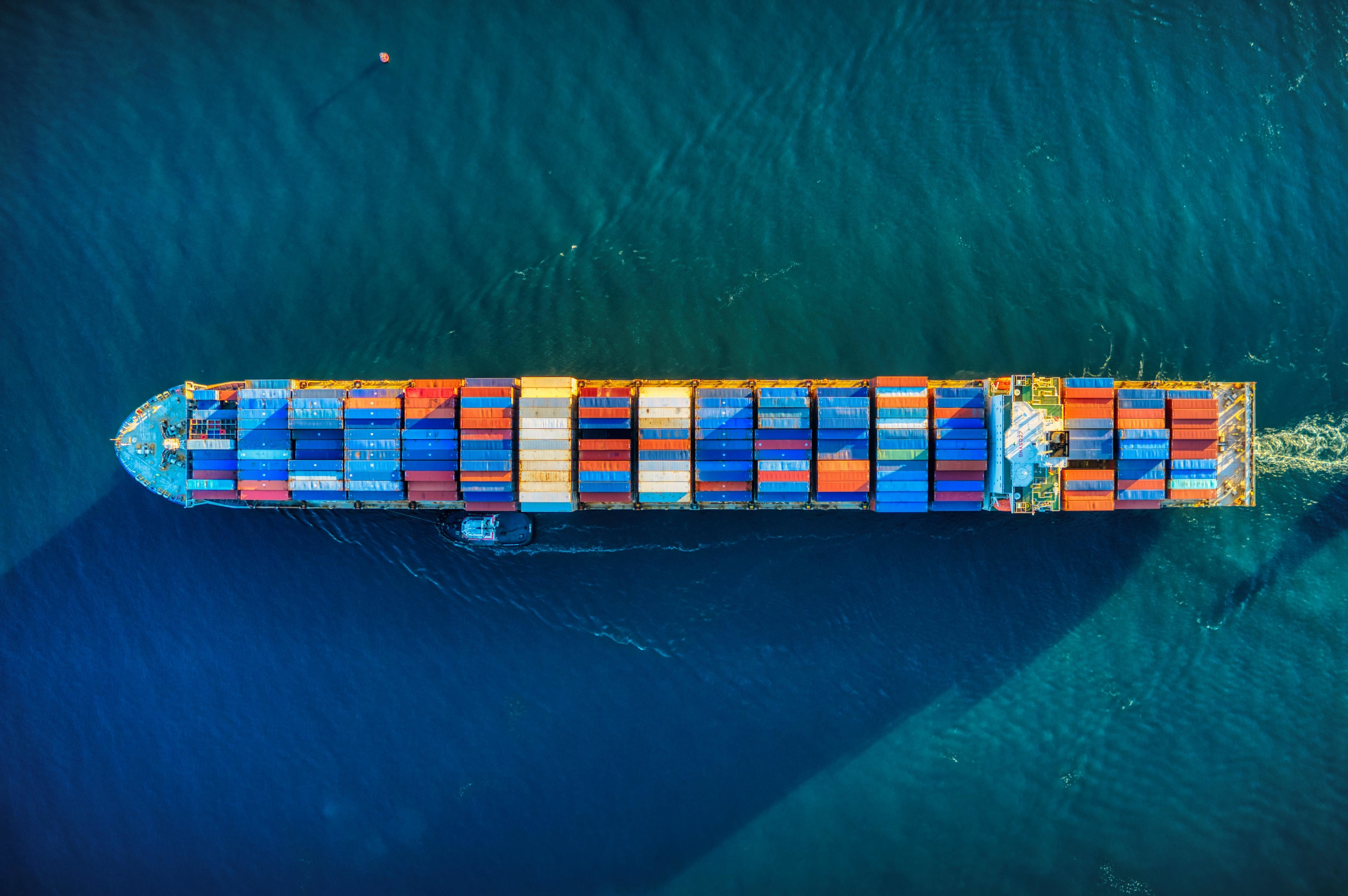 Large ship with containers, sea, overhead shot; supply chain, transportation, freight, shipping.