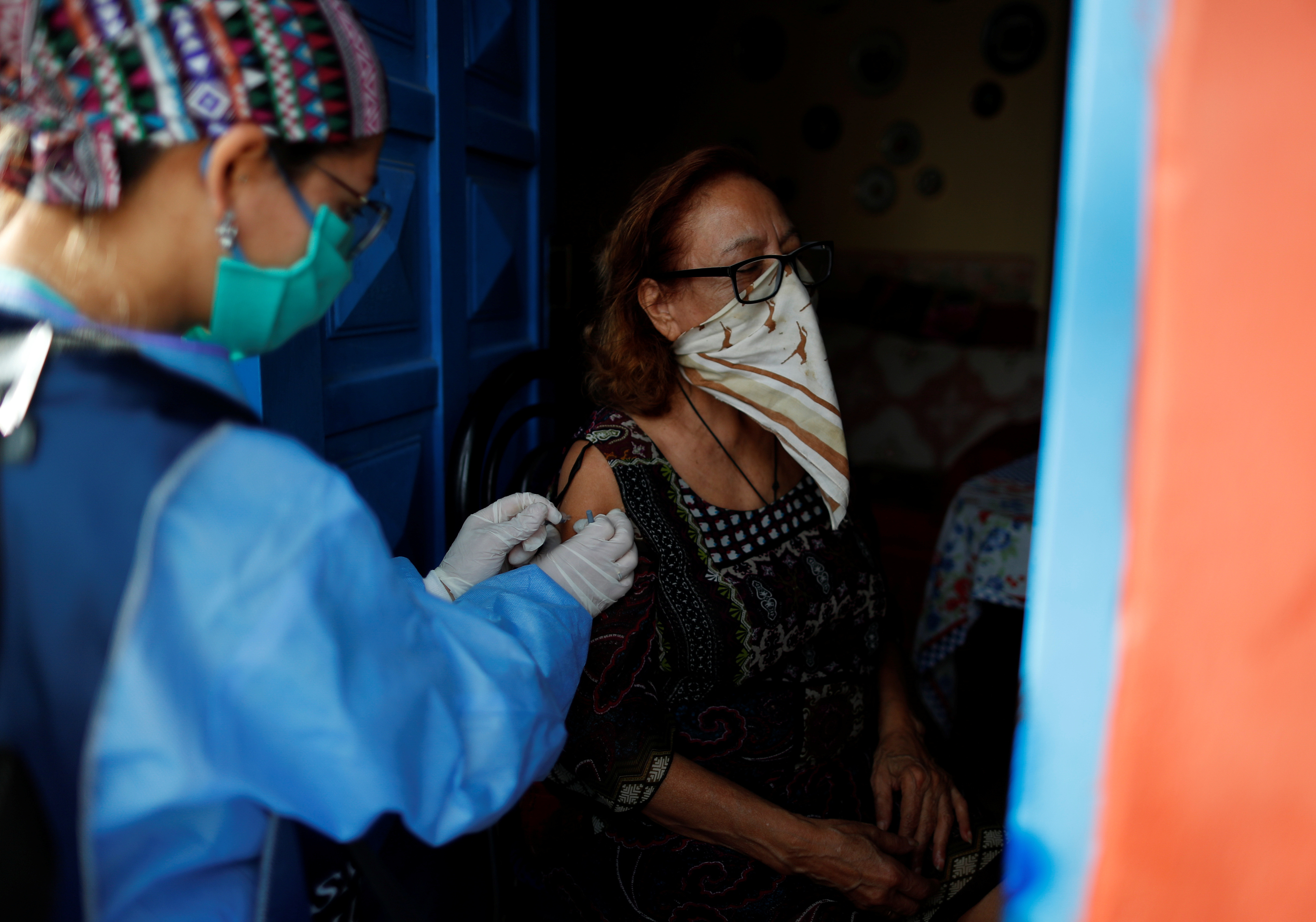 A healthcare worker vaccinates a woman as part of the start of the seasonal flu vaccination campaign as a preventive measure due to the outbreak of coronavirus disease (COVID-19), in Beccar, on the outskirts of Buenos Aires, Argentina June 17, 2020. Picture taken June 17, 2020. REUTERS/Agustin Marcarian - RC2UGH9D3XNT