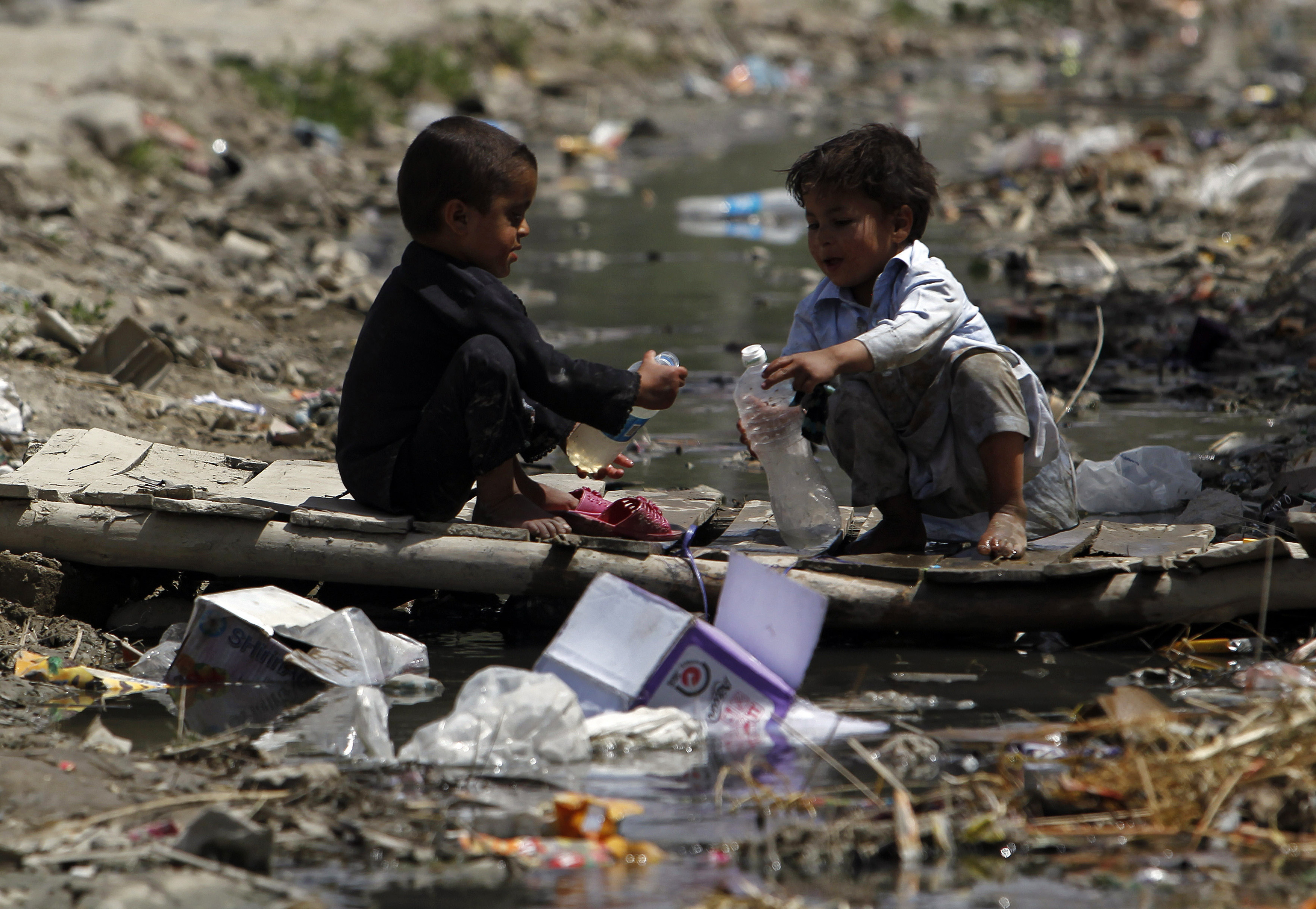 two boys play among some plastic pollution