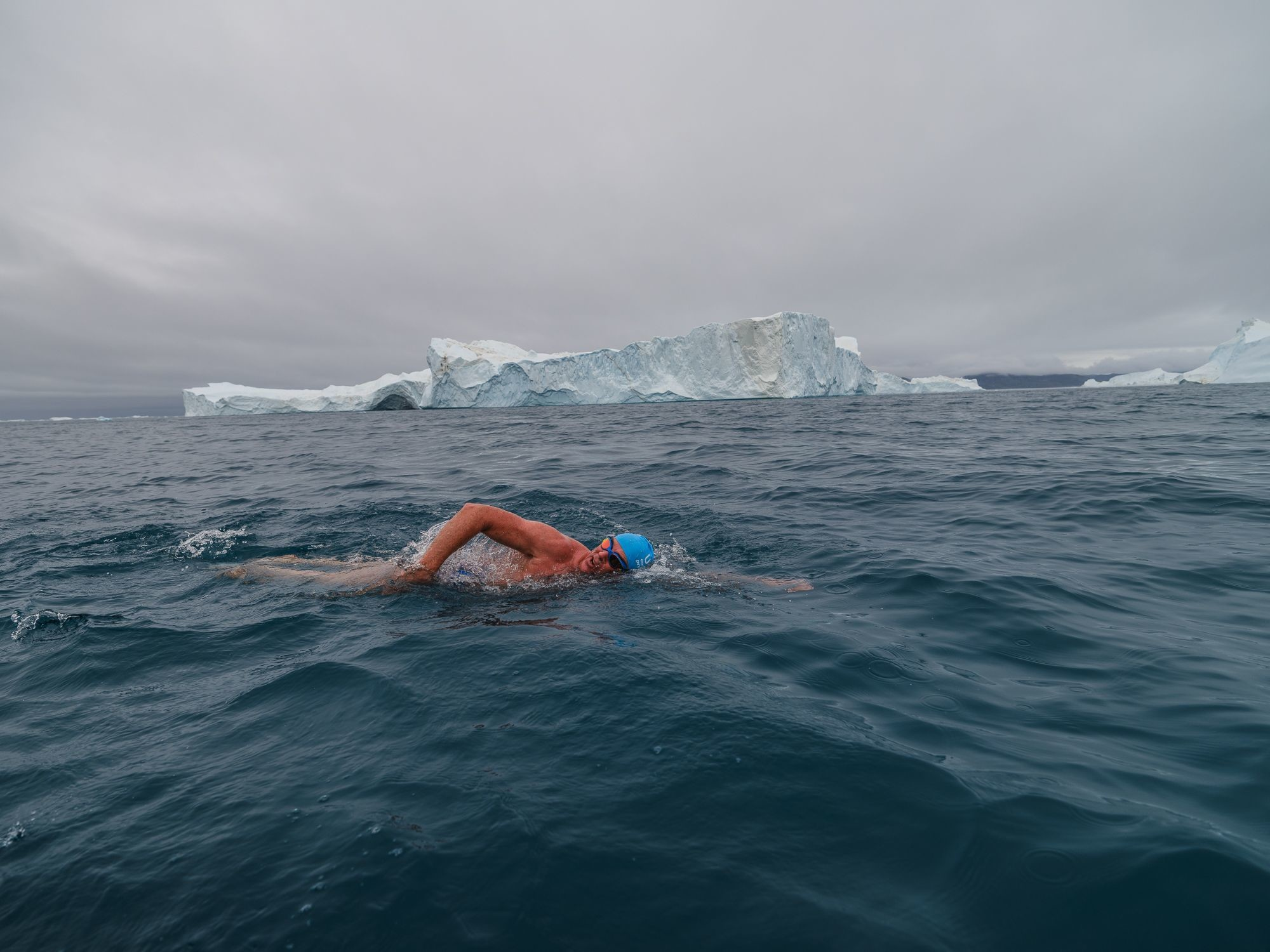 Lewis Pugh is pictured swimming past an iceberg, as part of his series of extreme swims to raise awareness of climate change.