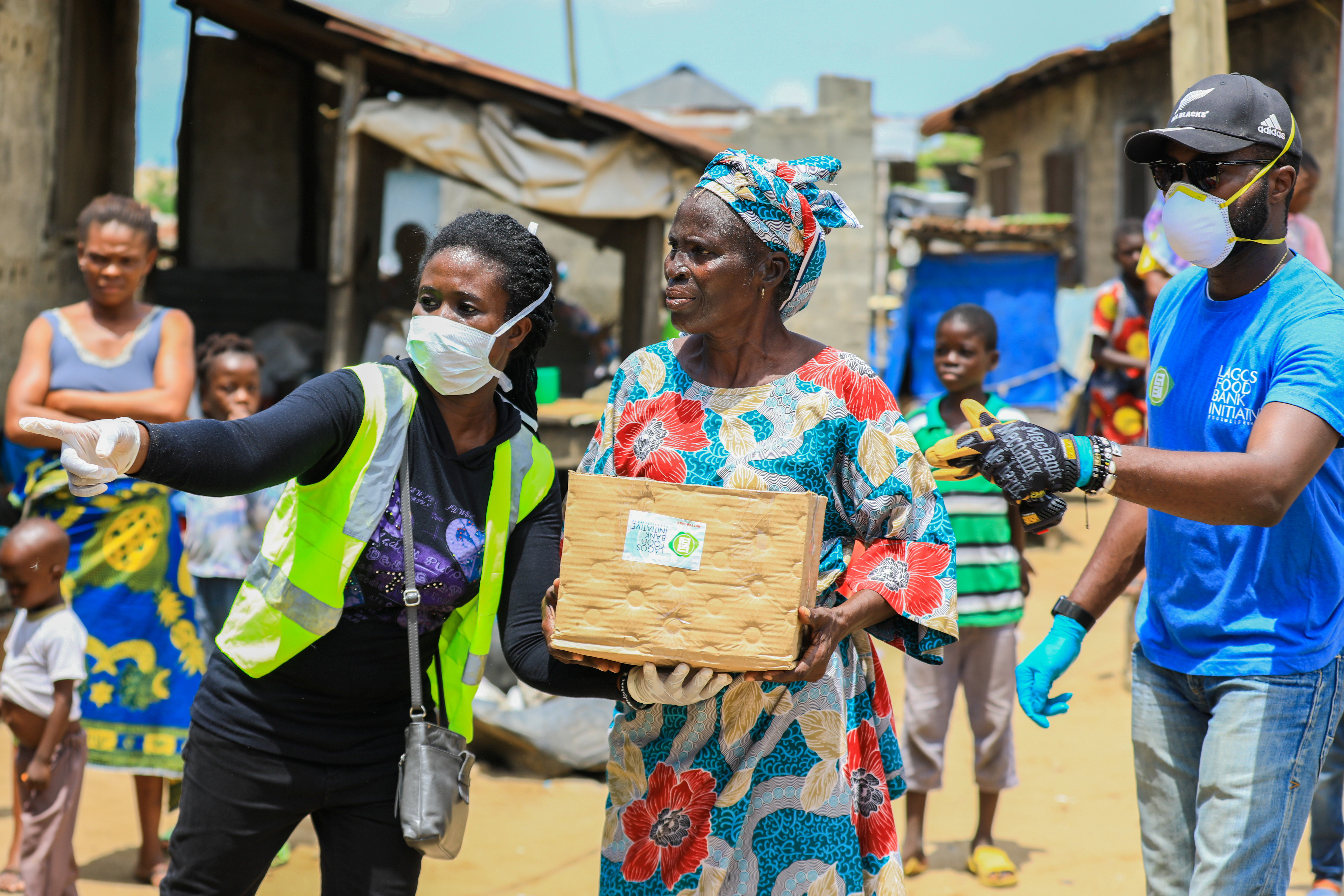 Volunteers gesture as they direct an elderly woman at an ongoing distribution of food parcels, during a lockdown by the authories in efforts to slow the spread of the coronavirus disease (COVID-19), in Lagos, Nigeria April 9, 2020. Picture taken April 9, 2020. REUTERS/Temilade Ade - RC2L5G9T8QZW