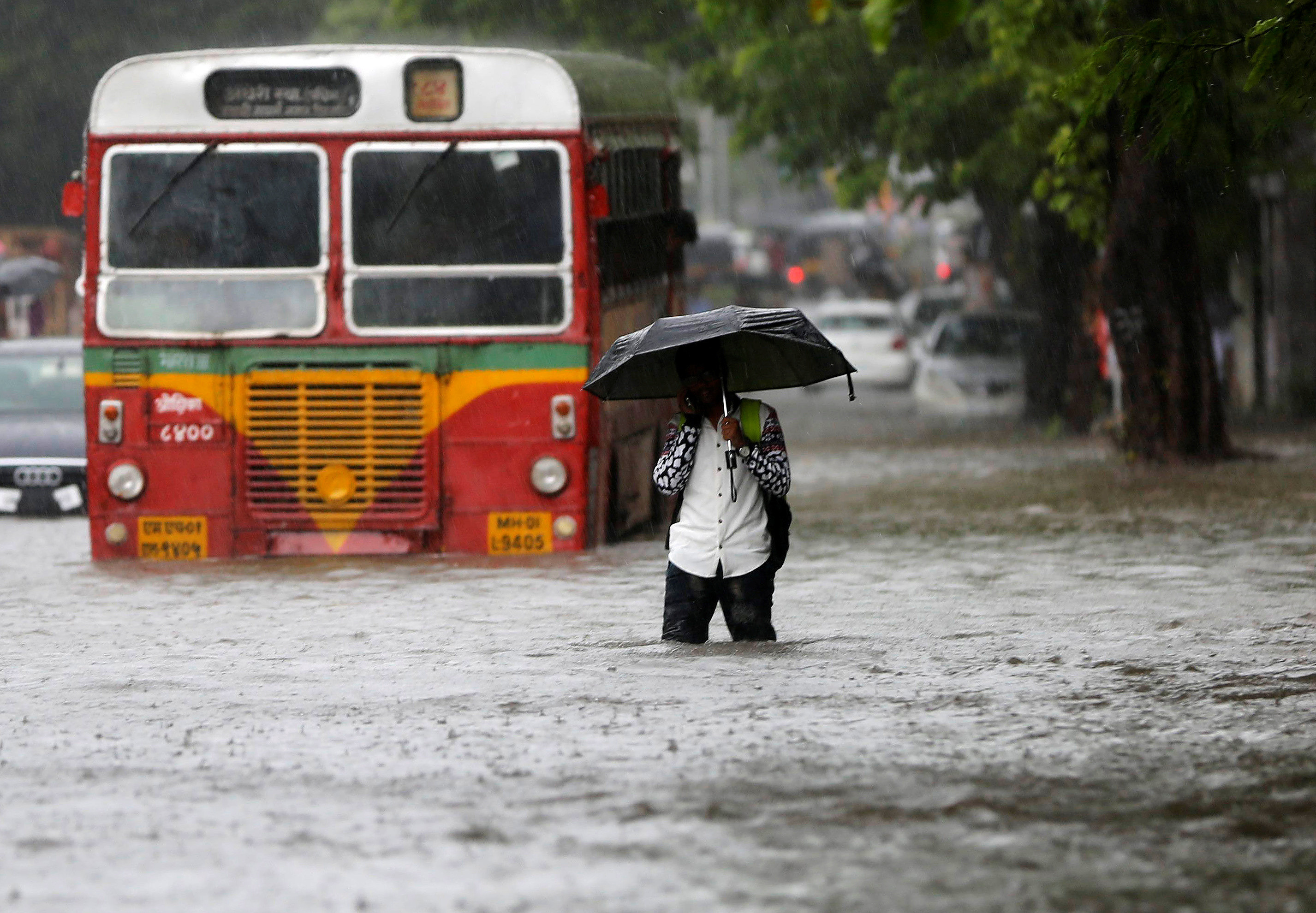 A man walks past a stranded public transport bus on a road flooded by heavy rains in Mumbai, India, August 5, 2016.