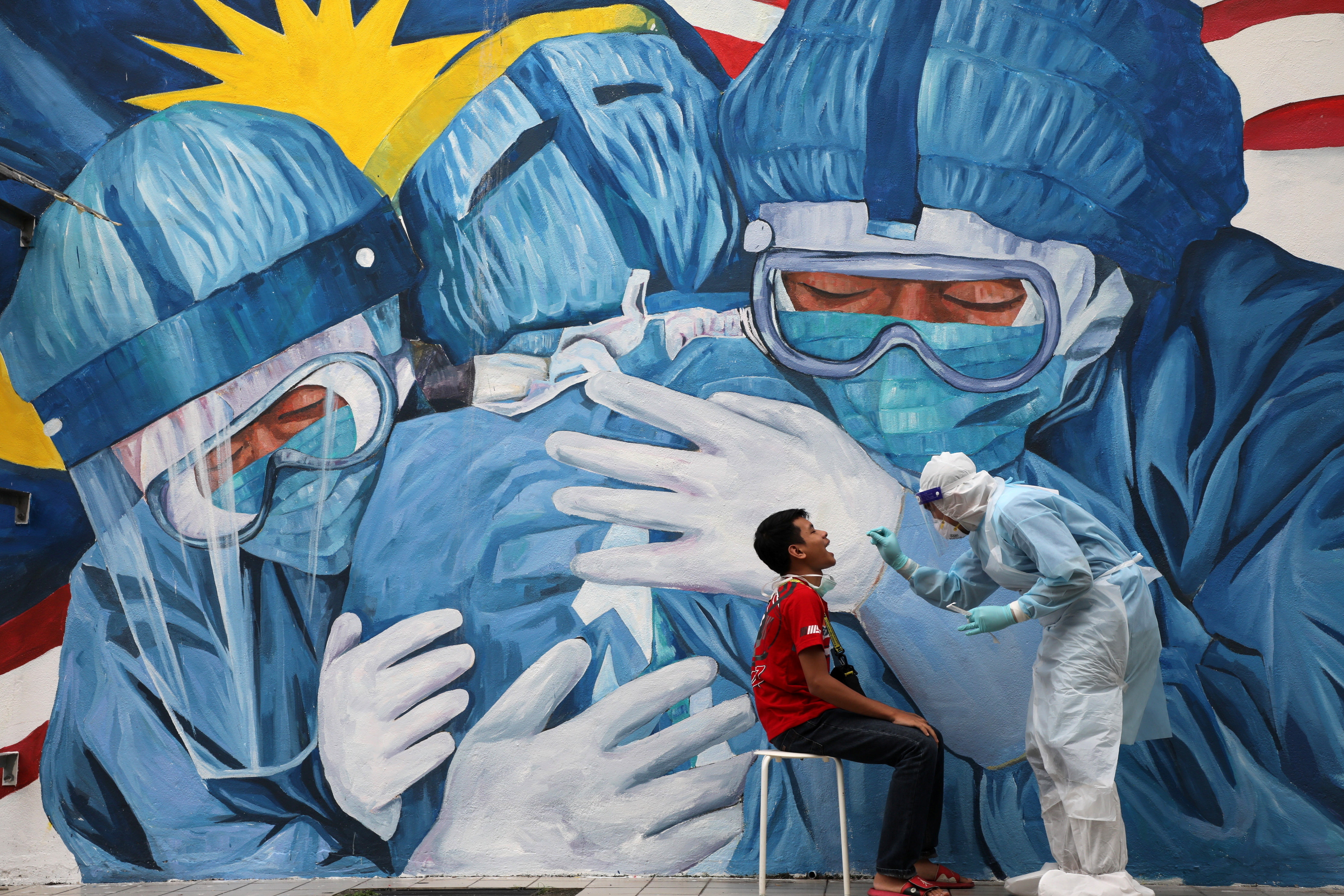 A doctor collects a swab sample from a man to be tested for the coronavirus disease against a mural depicting solidarity among healthcare workers.