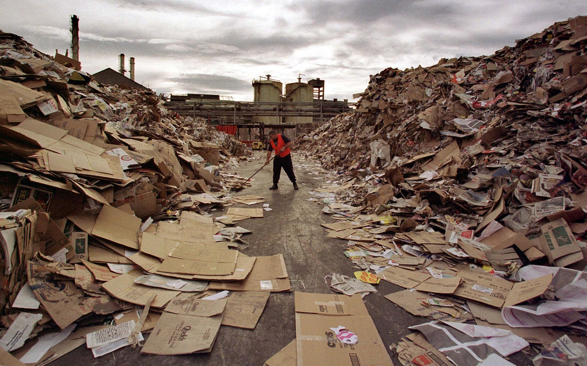 A worker cleans a path through the tonnes of waste paper awaiting recycling at Australia's largest paper recycling mill in Sydney. Prices for recycling paper, plastic and bottles have fallen so far in the last year that Australia is paying Indonesia to accept some of the A$100 million (US$76 million) a year industry. Picture taken 6JUN97. - PBEAHUMMQBD