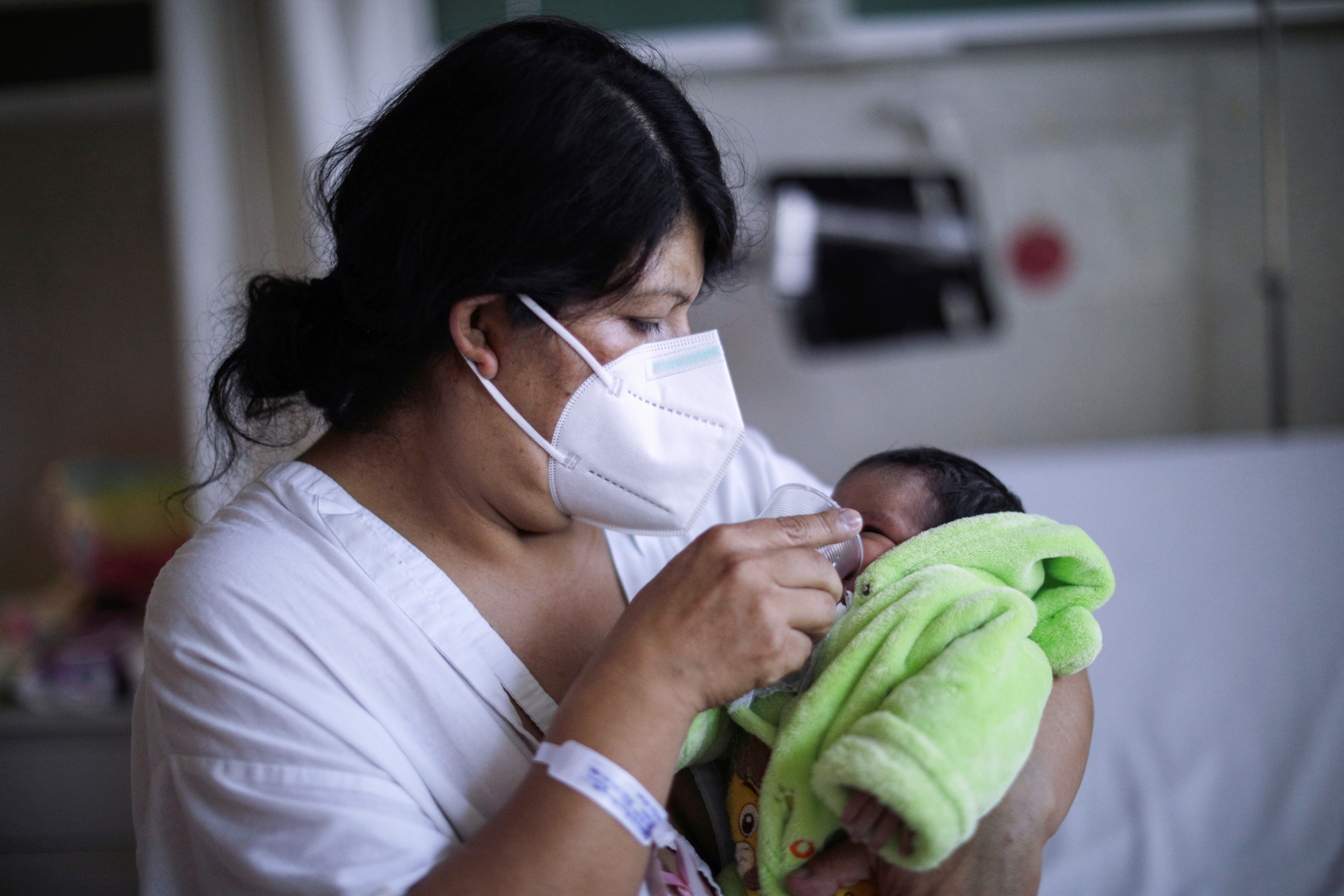 A woman infected with the coronavirus disease (COVID-19) carries her baby at the maternity ward for mothers infected with the coronavirus, at the Maternal Perinatal Hospital 'Monica Pretelini Saenz', in Toluca, Mexico February 4, 2021. REUTERS/Luis Cortes - RC22ML93Y8ZP