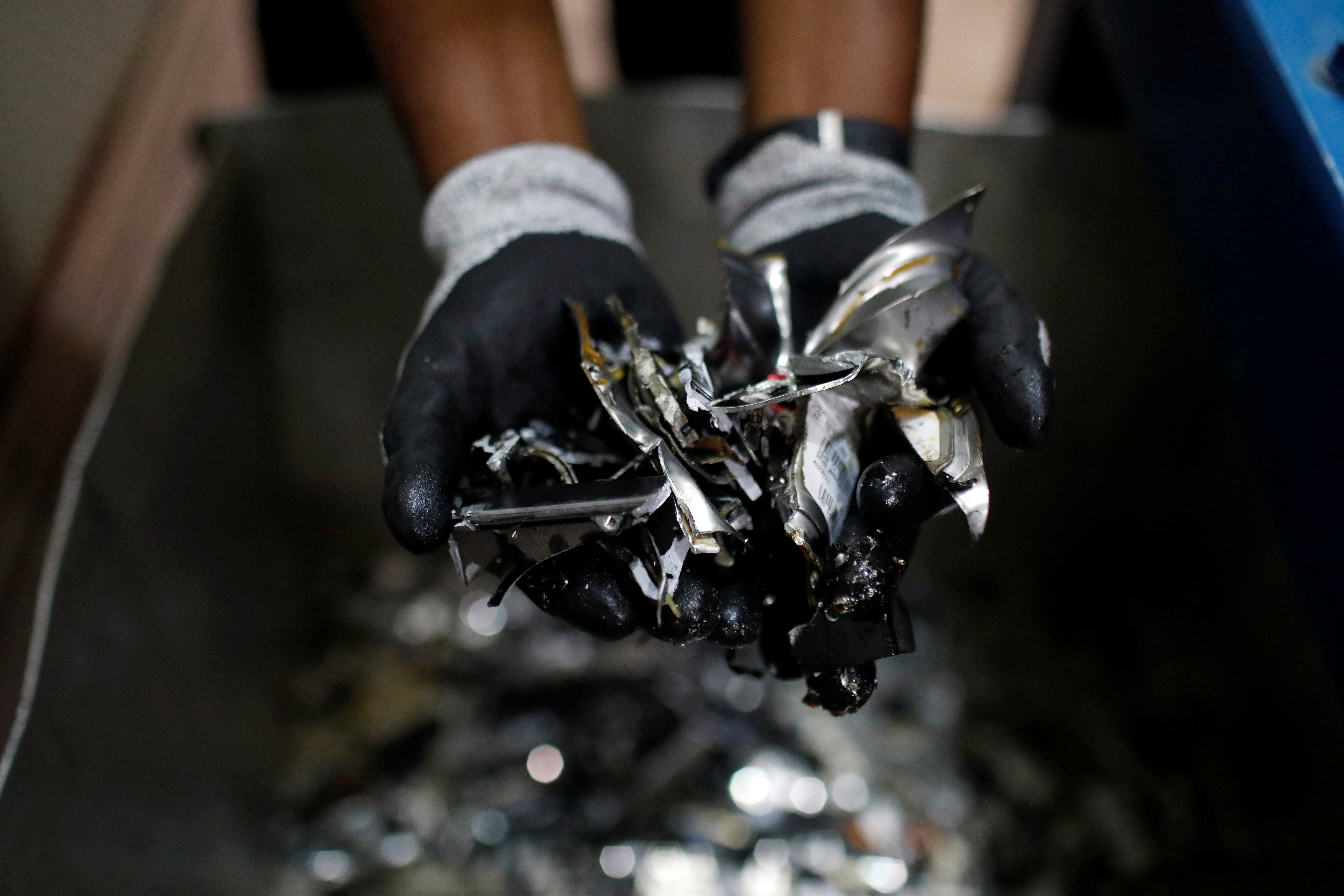 An employee displays a handful of shredded hard drive pieces, for e-waste processing, at E-Terra Matter Recovery and Recycling Facility in Festac, Lagos, Nigeria June 19, 2020. Picture taken June 19, 2020. REUTERS/Temilade Adelaja - RC2CYH9YMIGJ