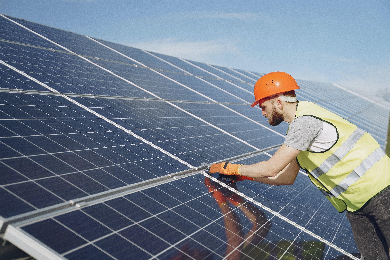 Man wearing hard hat fixing solar panels.