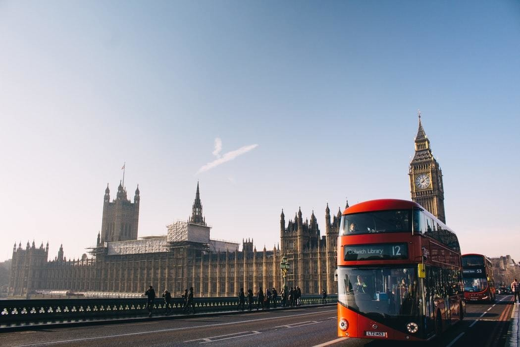 A red London bus is seen on London Bridge, in front of big ben and the houses of Parliament.