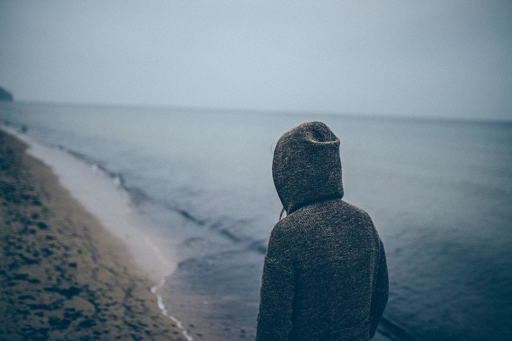 Person in a hoodie looks away from camera with sea in background.