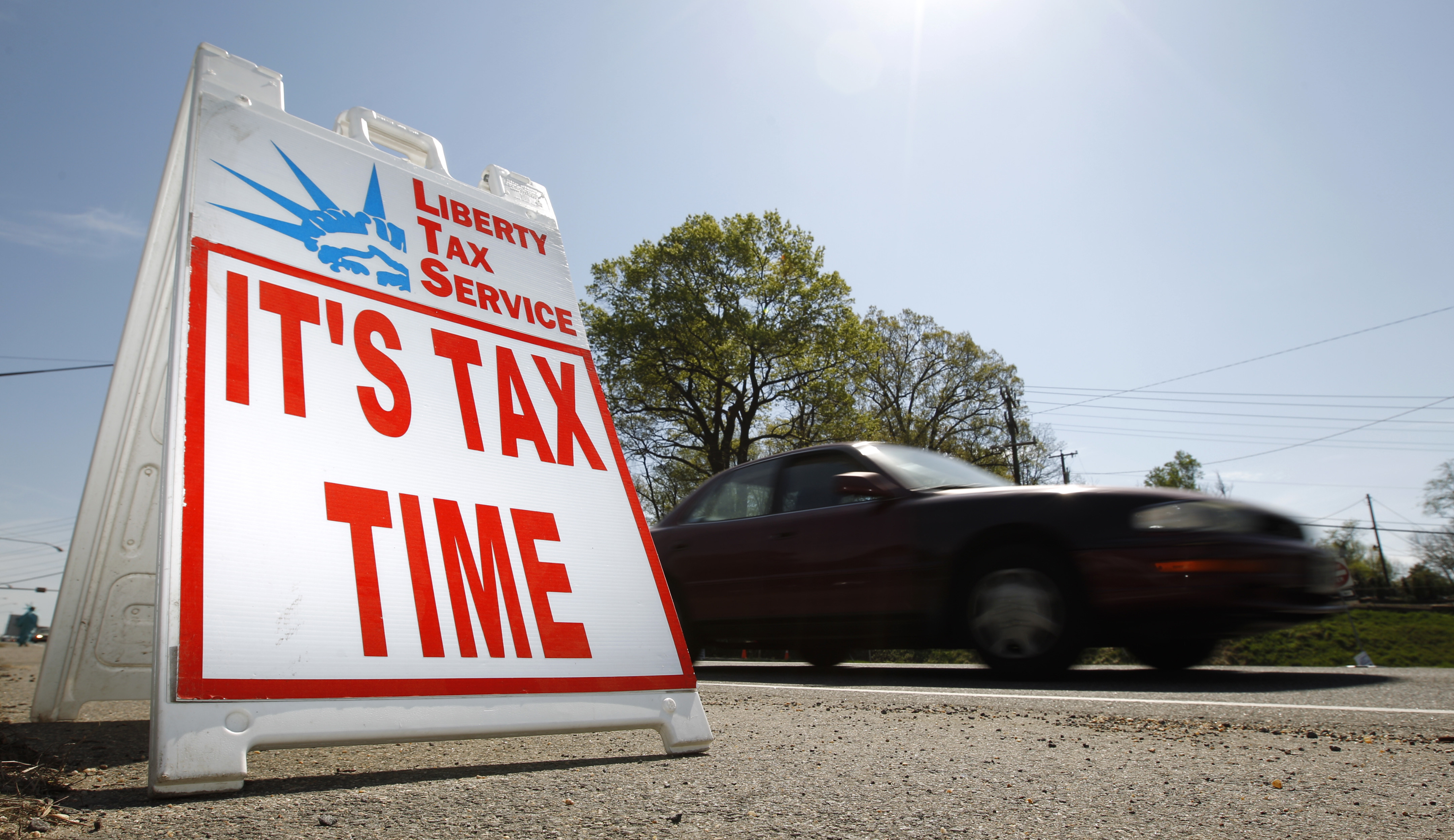 A car passes a sign advertising sign that says 'It's Tax Time'.