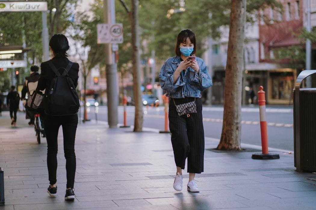 image of a woman walking in a city wearing a mask
