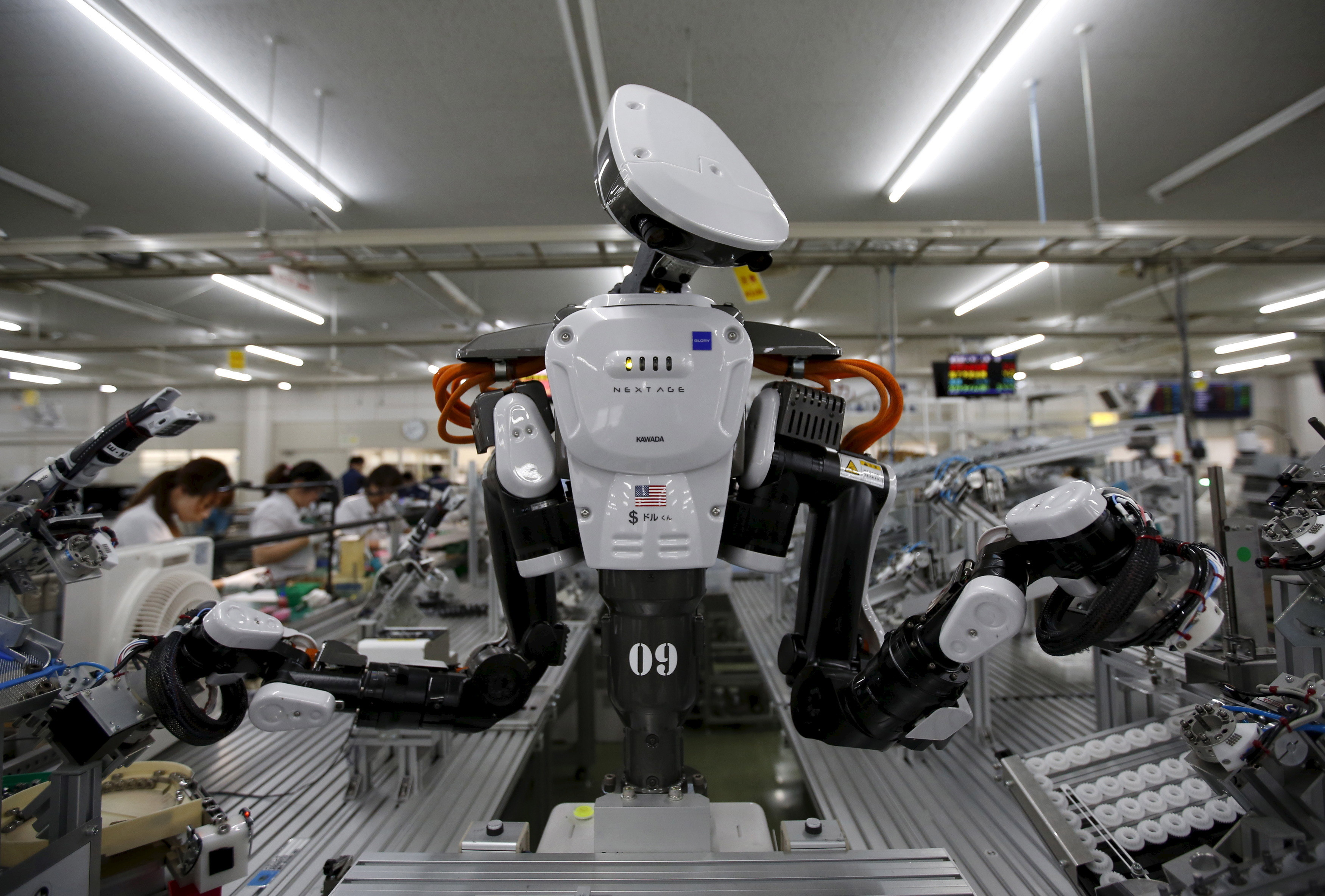 A humanoid robot works side by side with employees in the assembly line at a factory of Glory Ltd., a manufacturer of automatic change dispensers, in Kazo, north of Tokyo, Japan, July 1, 2015. Japanese firms are ramping up spending on robotics and automation, responding at last to premier Shinzo Abe's efforts to stimulate the economy and end two decades of stagnation and deflation. Picture taken July 1, 2015. REUTERS/Issei Kato      TPX IMAGES OF THE DAY      - GF10000147191