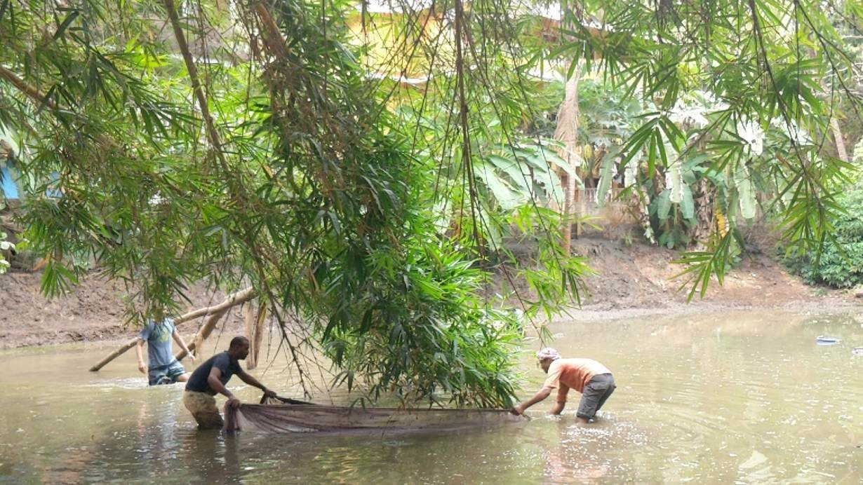 Migrant workers clean a pond in western state of Goa, India.