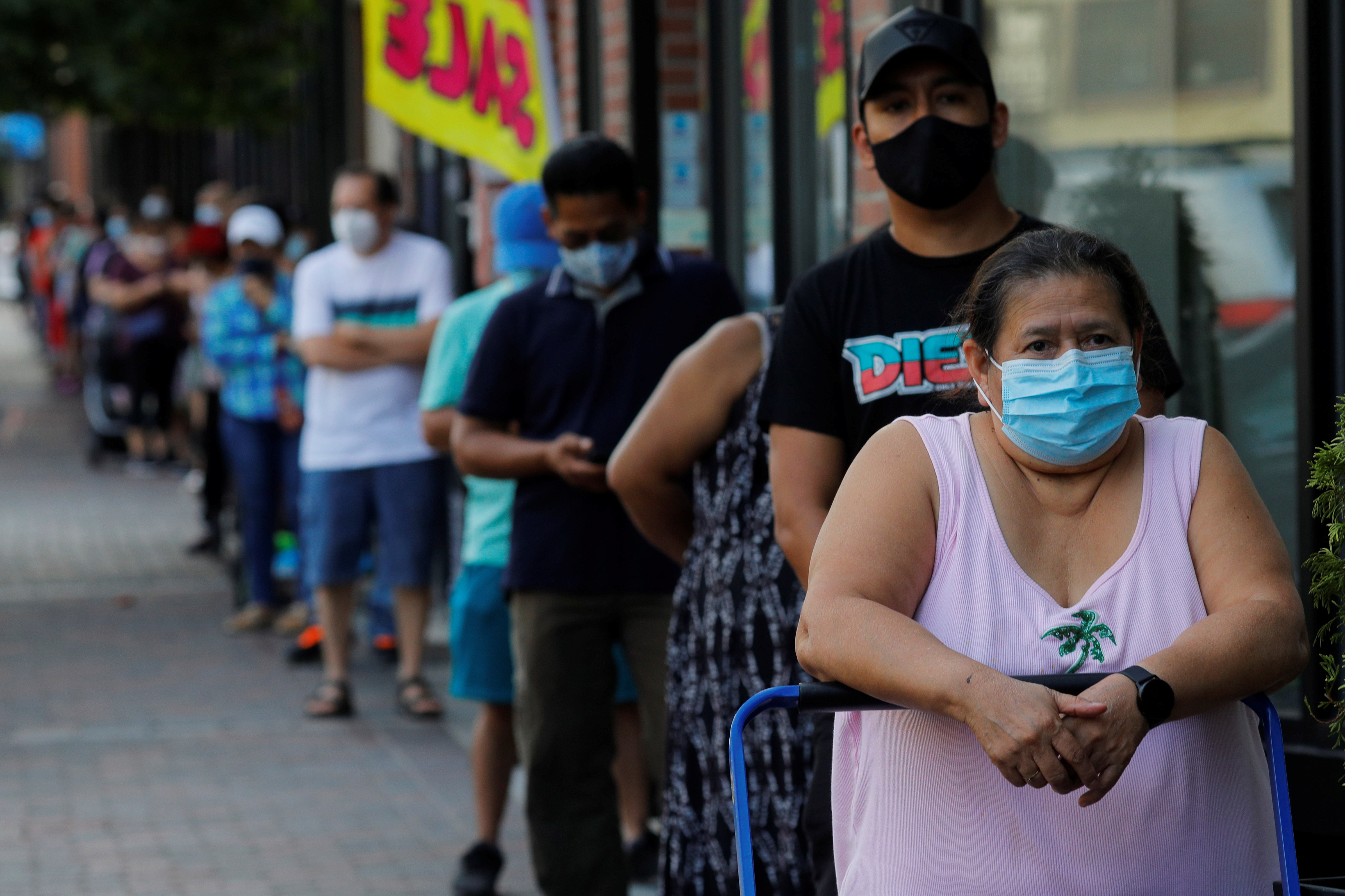 People wait in line for free groceries distributed by the Chelsea Collaborative in a city hard hit by the coronavirus disease (COVID-19) outbreak, in Chelsea, Massachusetts, U.S., July 22, 2020.   REUTERS/Brian Snyder - RC2OYH9PQJK8