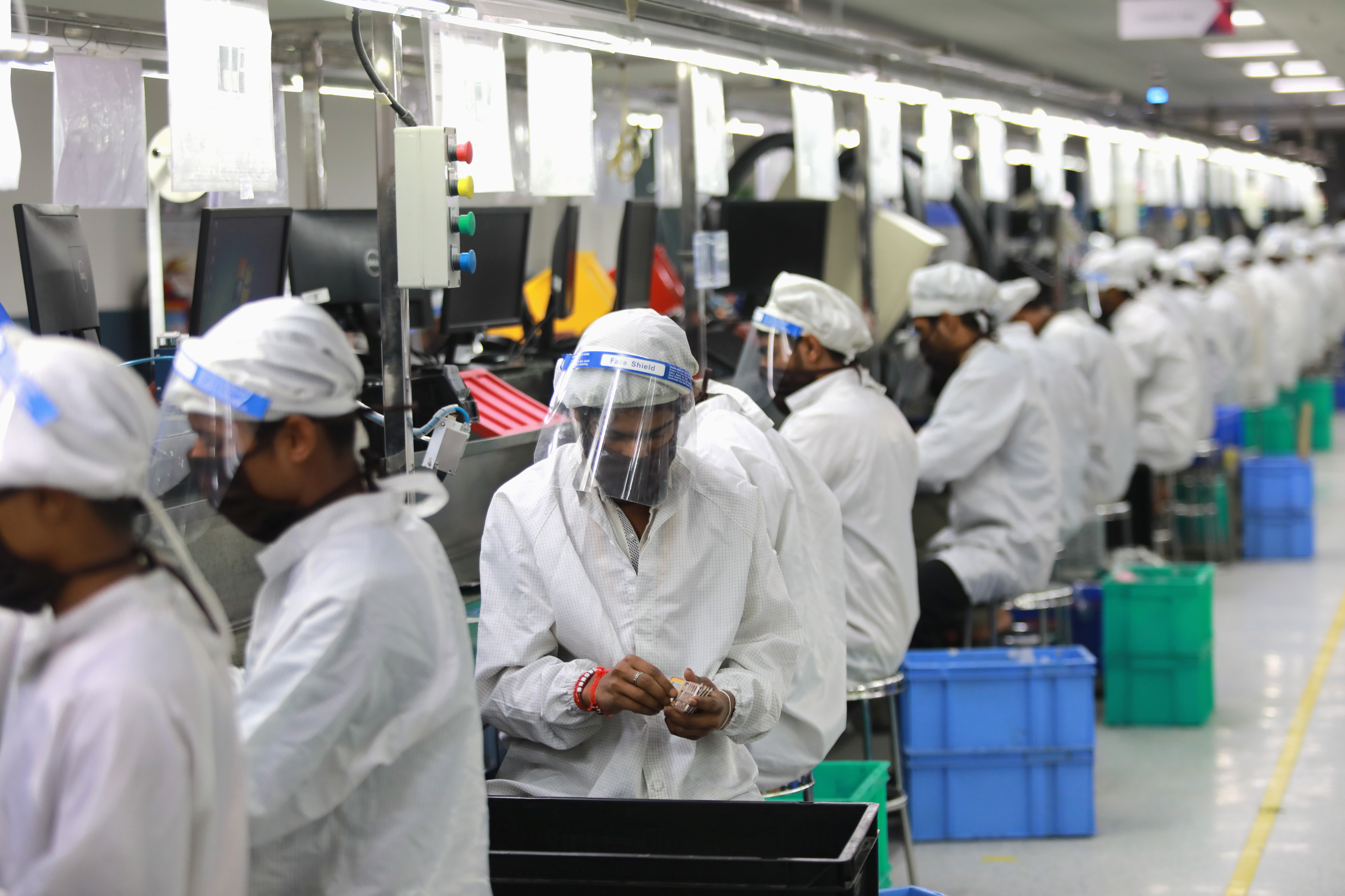 Workers wearing face shields work at an assembly line of mobile phones at Lava International Limited's manufacturing plant, after some restrictions were lifted during an extended nationwide lockdown to slow the spread of the coronavirus disease (COVID-19) in Noida, India, May 12, 2020. Picture taken  May 12, 2020. REUTERS/Anushree Fadnavis - RC2FNG903YU7