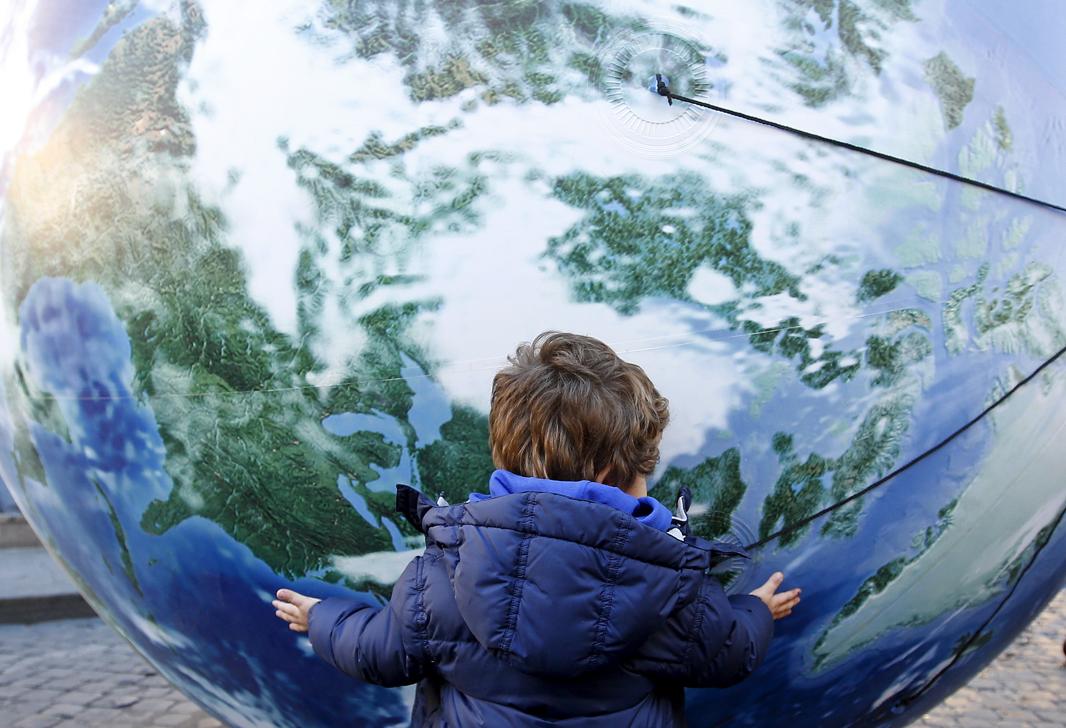 A child embraces a globe shaped balloon during a rally held ahead of the start of the 2015 Paris World Climate Change Conference, known as the COP21 summit, in Rome, Italy , November 29, 2015. REUTERS/Alessandro Bianchi - GF20000078554