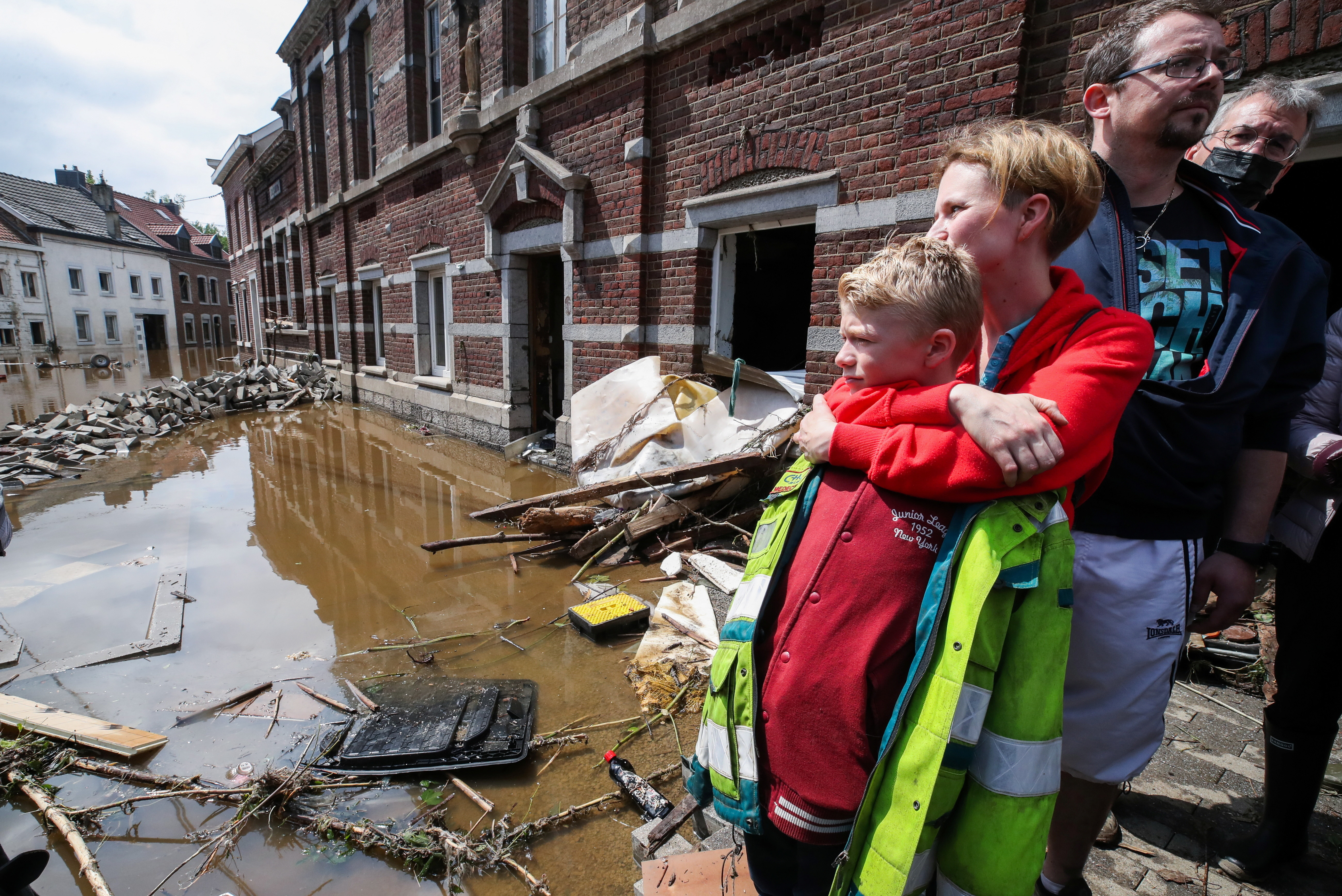 Madeline Brasseur, 37, Paul Brasseur, 42, with their son Samuel, 12, embrace each other at an area affected by floods, following heavy rainfalls, in Pepinster, Belgium, July 17, 2021. REUTERS/Yves Herman - RC2CMO9IMGTC